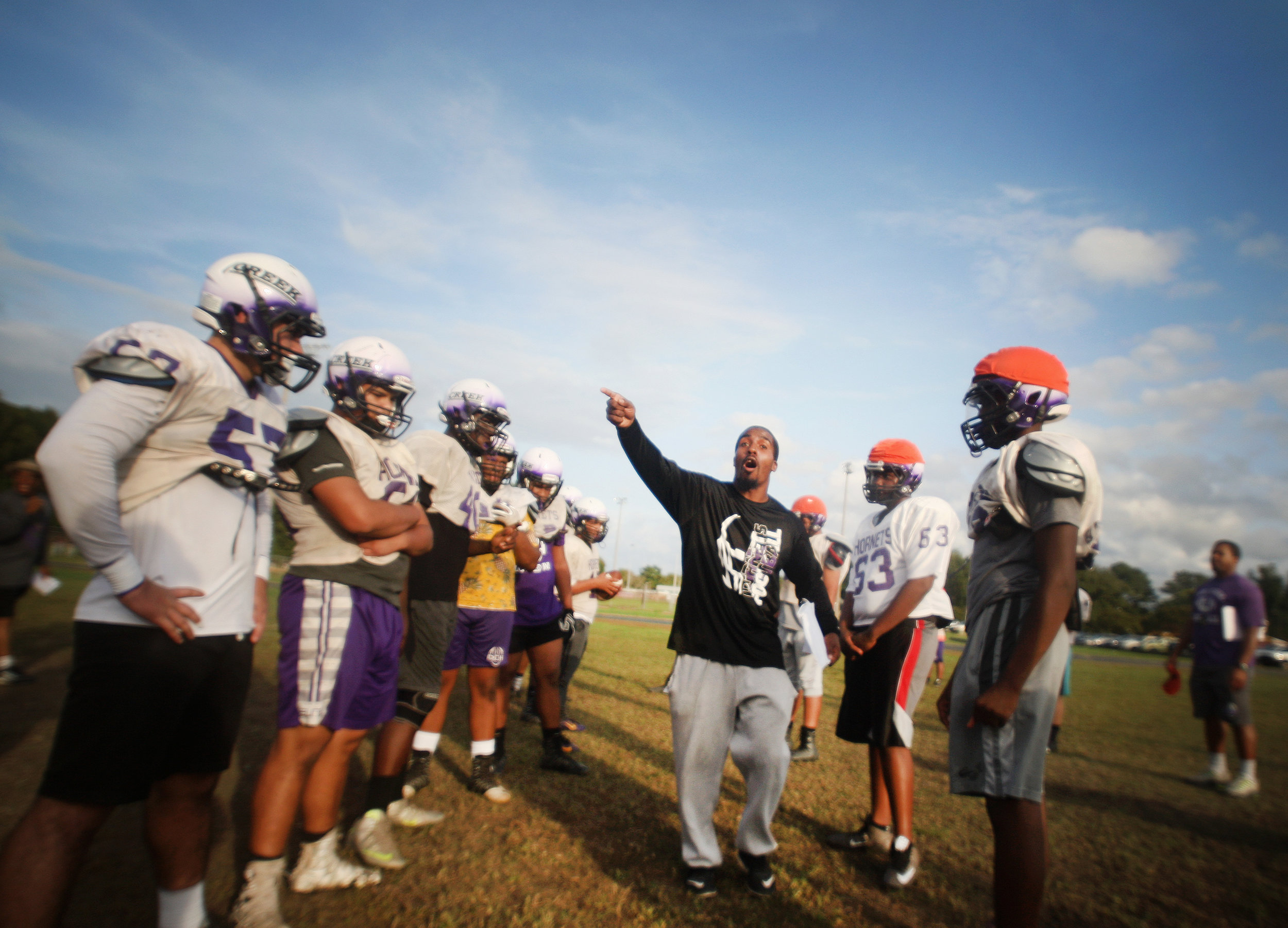 Deep Creek head coach Andre Twine talks with his team during practice, Monday, Oct. 9, 2017 at Deep Creek High School in Chesapeake. After nearly a decade in the basement, Twine has quickly turned things around for the Hornets program.