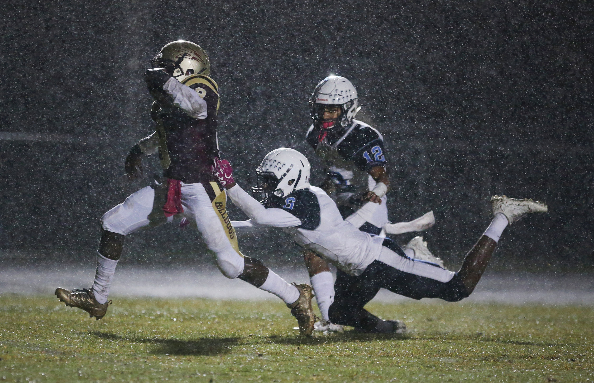On a rain-soaked night, King's Fork's Darran Butts breaks past Indian River's Demetri Payne, center, and Isaiah Hyman for a first quarter touchdown, Friday, Oct. 13, 2017 at King's Fork High School in Suffolk.