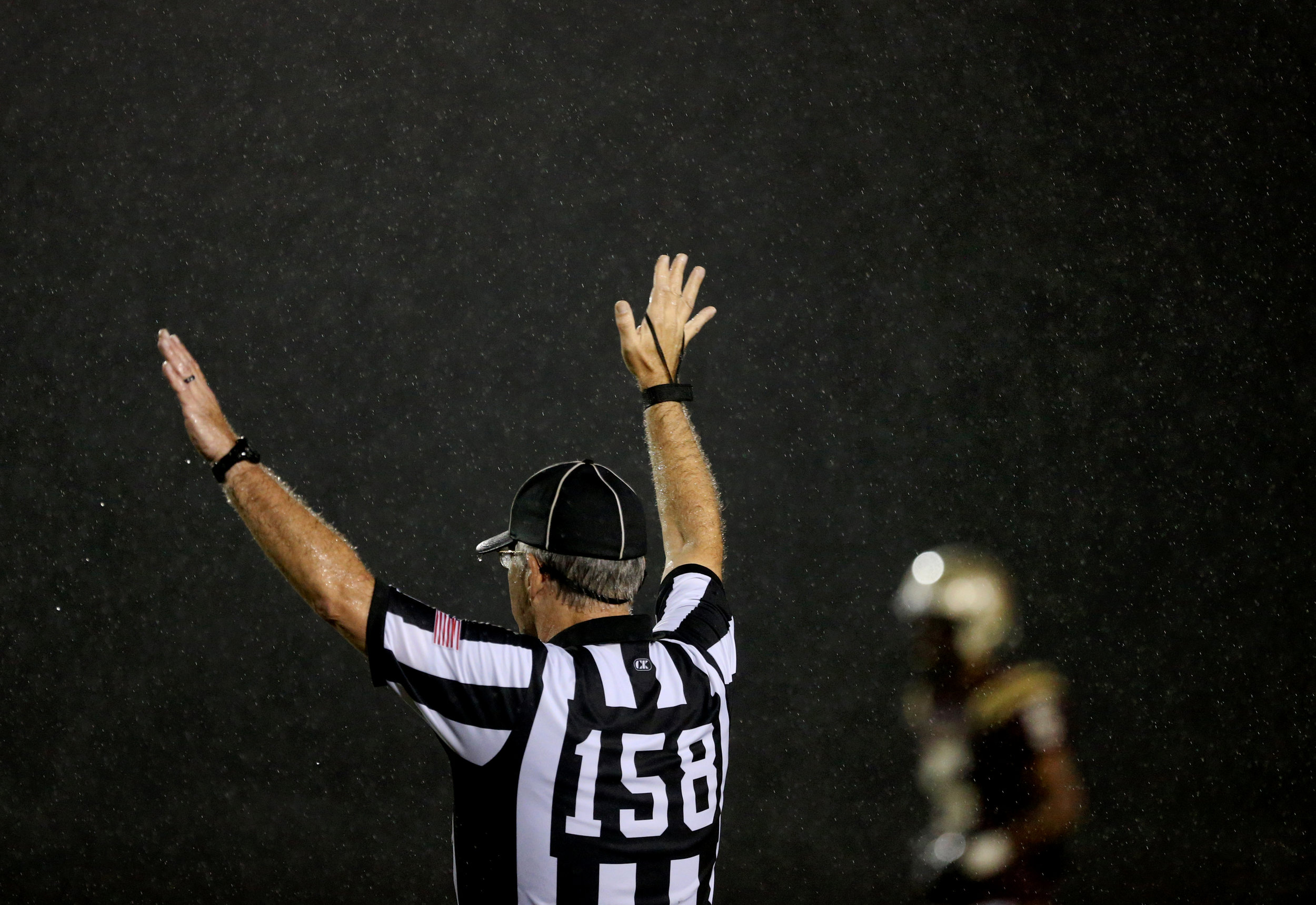 An official raises his arms to stop play during a driving rain in the game between King's Fork and Indian River, Friday, Oct. 13, 2017 in Suffolk.