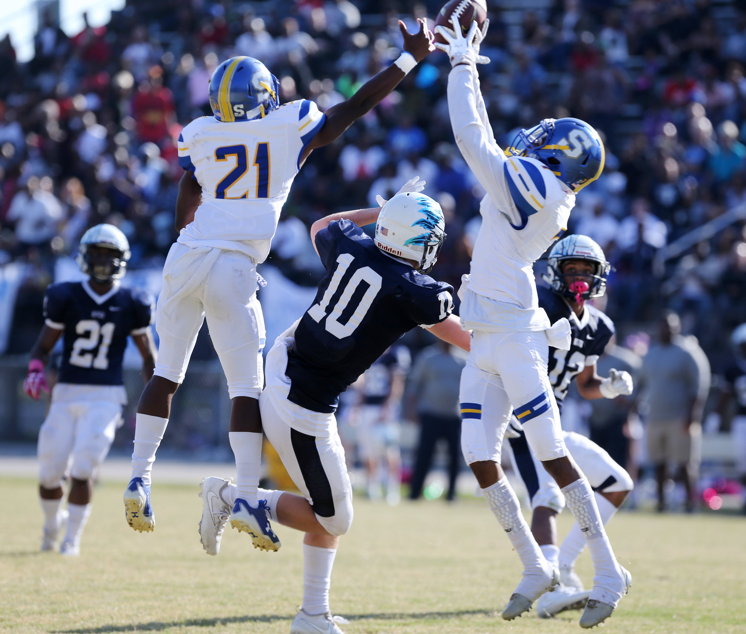 Oscar Smith's Jaylen Todd, right, picks off a pass intended for Indian River's Dylan Hammond, center, but the play was called back due to a penalty and the Braves would score on the ensuing play during the Tigers' 35-14 win, Saturday, Oct. 21, 2017 at Indian River High School in Chesapeake.