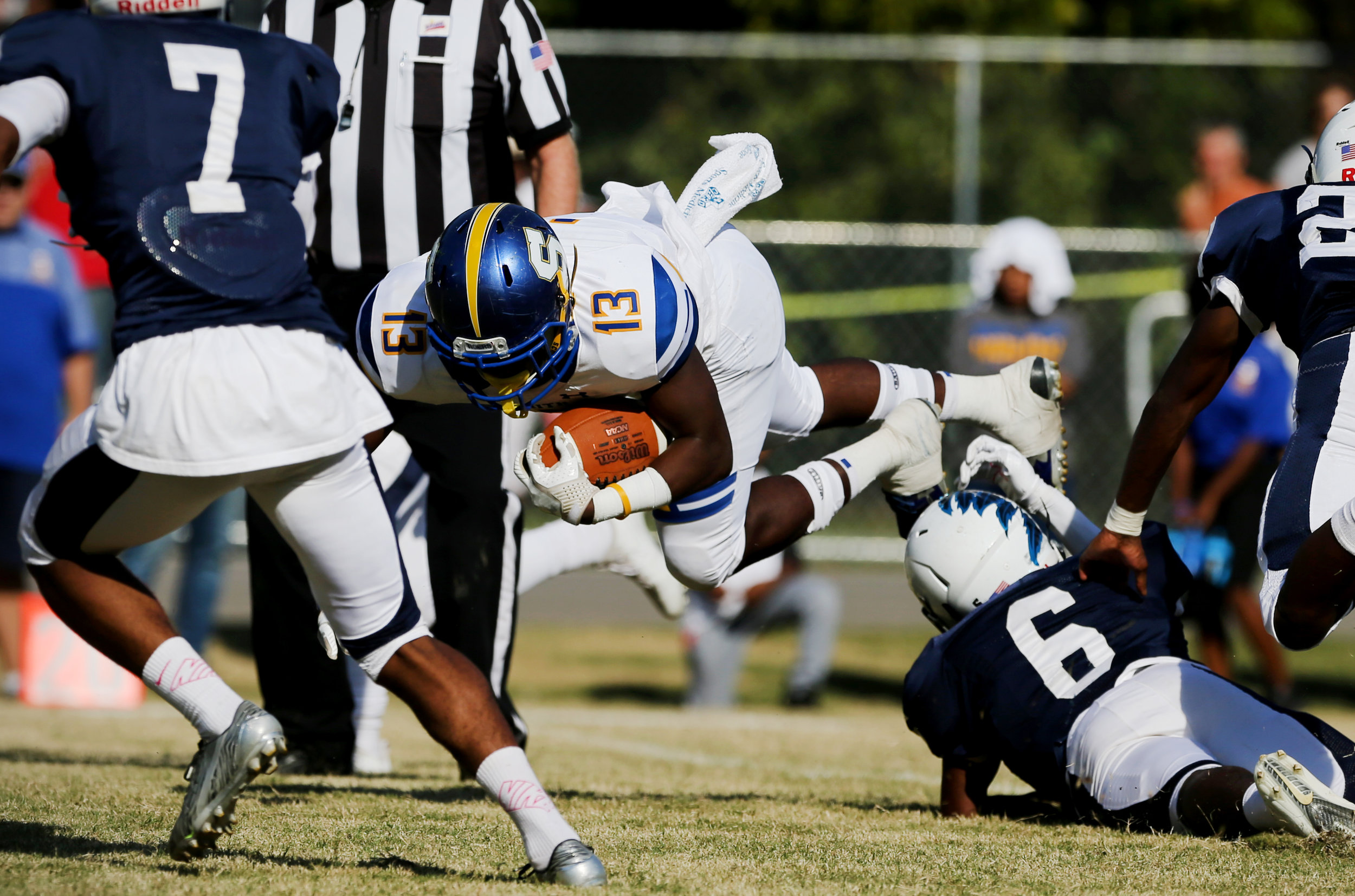 Oscar Smith's Deangelo White goes airborne after being tripped up by Indian River's Demetri Payne during the Tigers' 35-14 win, Saturday, Oct. 21, 2017 at Indian River High School in Chesapeake.