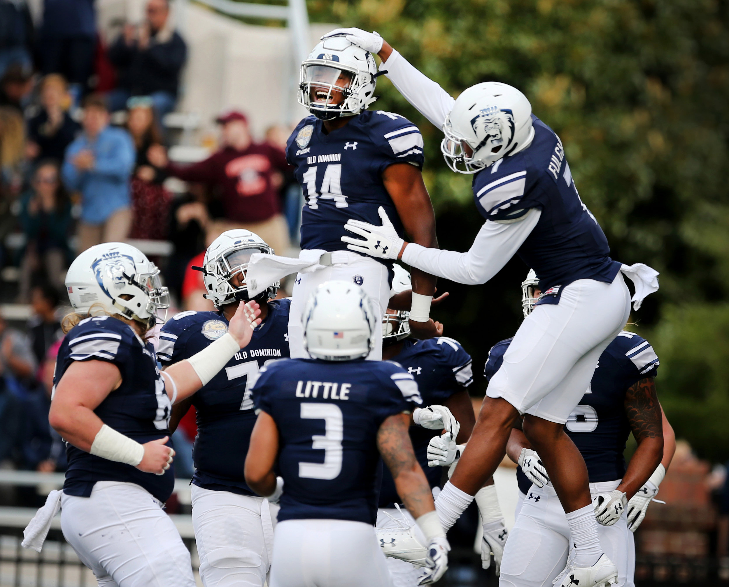 Old Dominion players celebrate with Steven Williams, Jr., center, after Williams ran the ball in on a quarterback keeper play for the first touchdown against Rice, Saturday, Nov. 18, 2017 at Foreman Field in Norfolk.