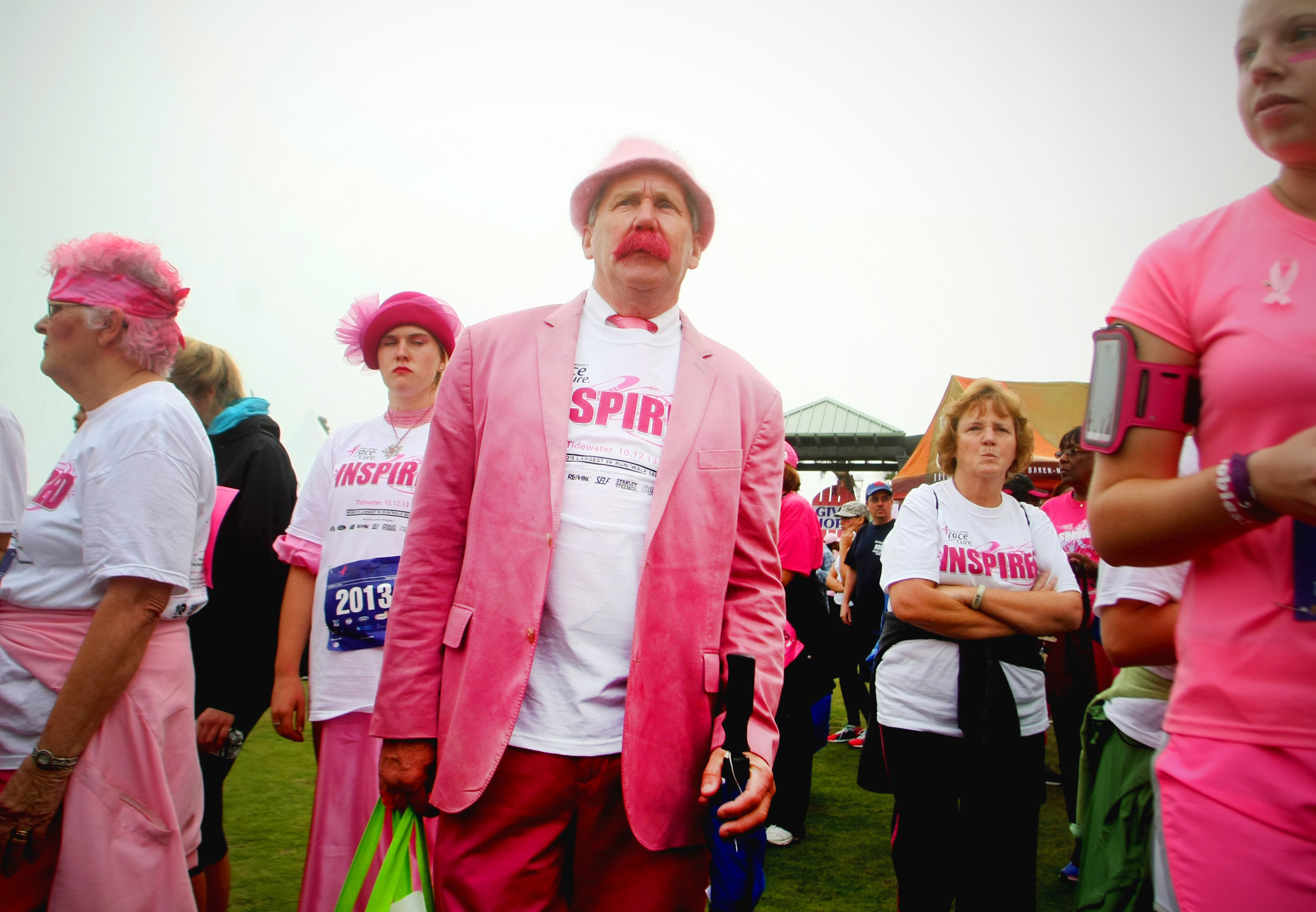 Tom Schlosser, center, of Chesapeake, looks for other family members to make their way to the starting line of the Komen Race For The Cure 5K