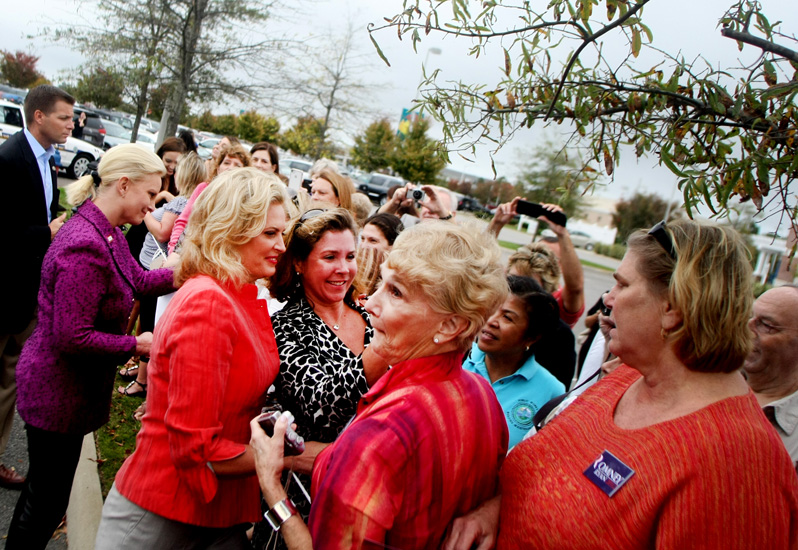 Ann Romney, left in red, and Cindy McCain, far left in purple, greet supporters during a campaign stop, Friday, Oct. 26, 2012 in Virginia Beach.