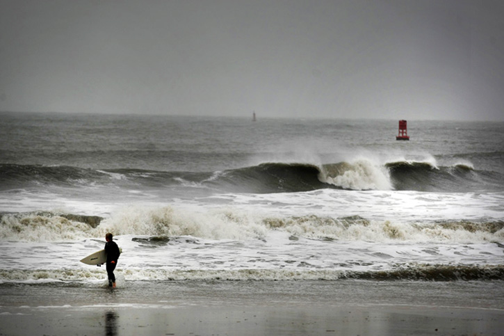 Todd Jarvis of Virginia Beach emerges from the surf after he determined that the currents were too hard to surf in as Hurricane Sandy pounded the Virginia coastline in Virginia Beach.