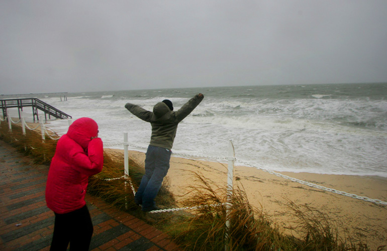 "Terrell Dwyer, 9, yelled ""I'm the king of the world"" as his sister Catherine Dwyer, left, shielded her eyes from the pounding surf brought by Hurricane Sandy along the Virginia coastline."