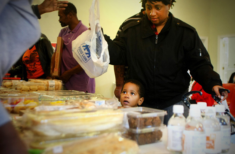 Tanya Elliot and her son Troy, 2, pick out the food they want at the Wesley Service Center in Portsmouth. The center gives away donated items to the needy.