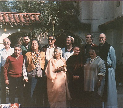 The 2nd Snowmass Conference at Ananda Ashram in La Crescenta, CA, 1985. Front Row: Swami Buddhananda, unknown observer, Gayatri Devi, Pema Chodron, Tania Lentov Back Row: unknown observer, Rabbi Rami Shapiro, Gerald Red Elk, Imam Bilal Hyde, Fr. George Timko, Fr. Thomas Keating OCSO. Photo by Roger La Borde.