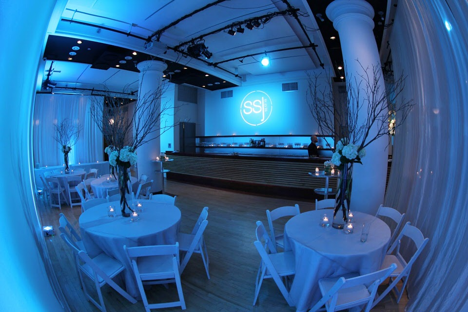 Sophia's Bat Mitzvah at HELEN MILLS - Tables with gorgeous centerpieces for the adult guests across from the bar. Sophia's custom gobo is projected above the bar area.