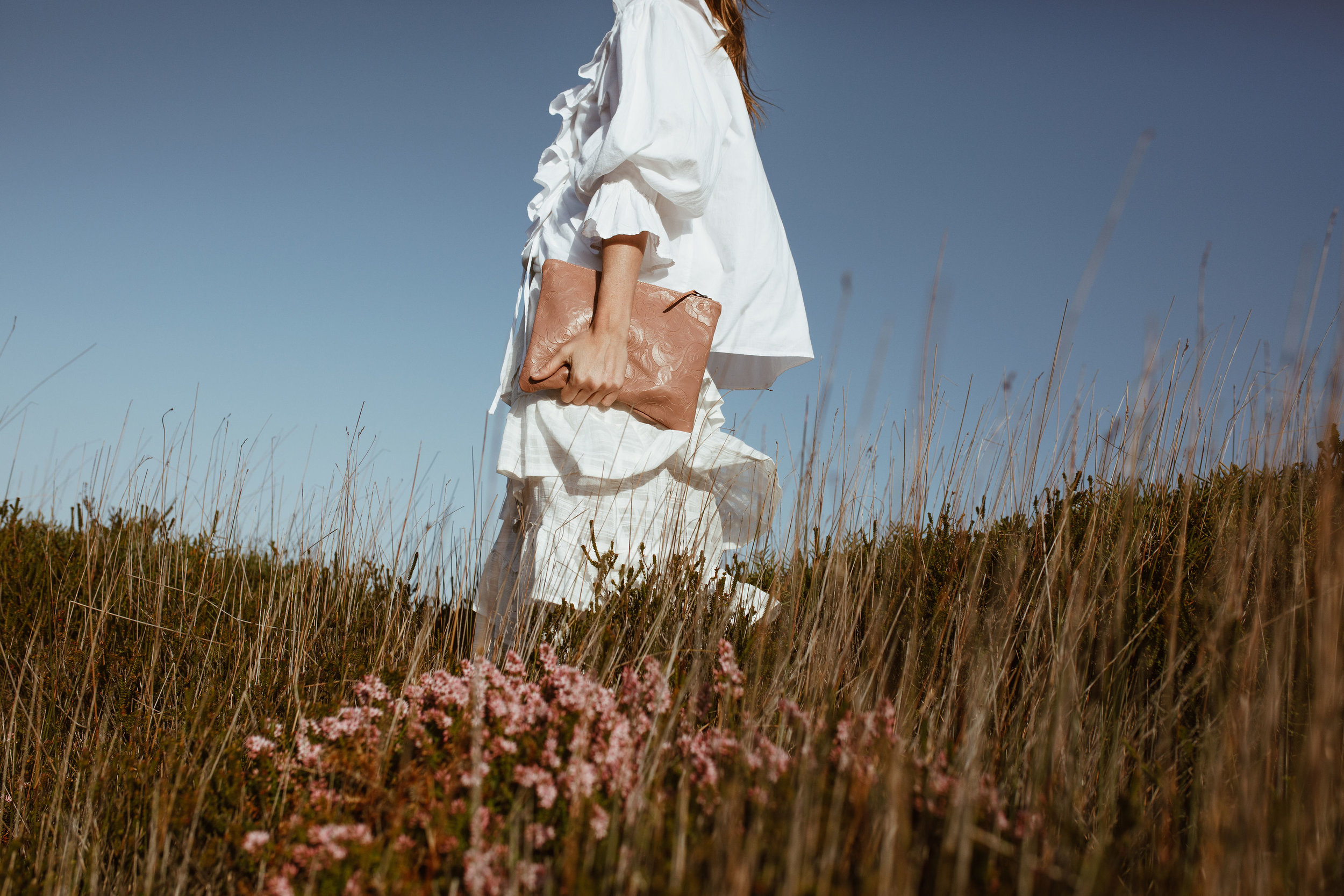 A woman in a white dress walking through a field with a blush KARMME leather clutch in her hand