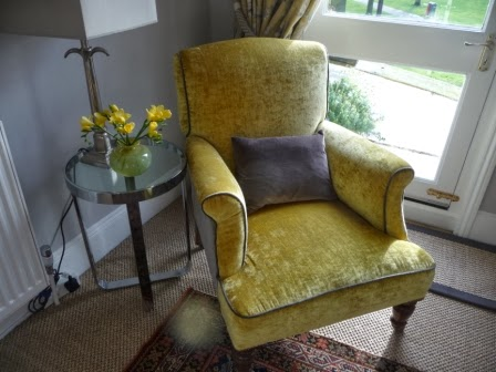 A vase of gold freesias to complement the gold velvet chair