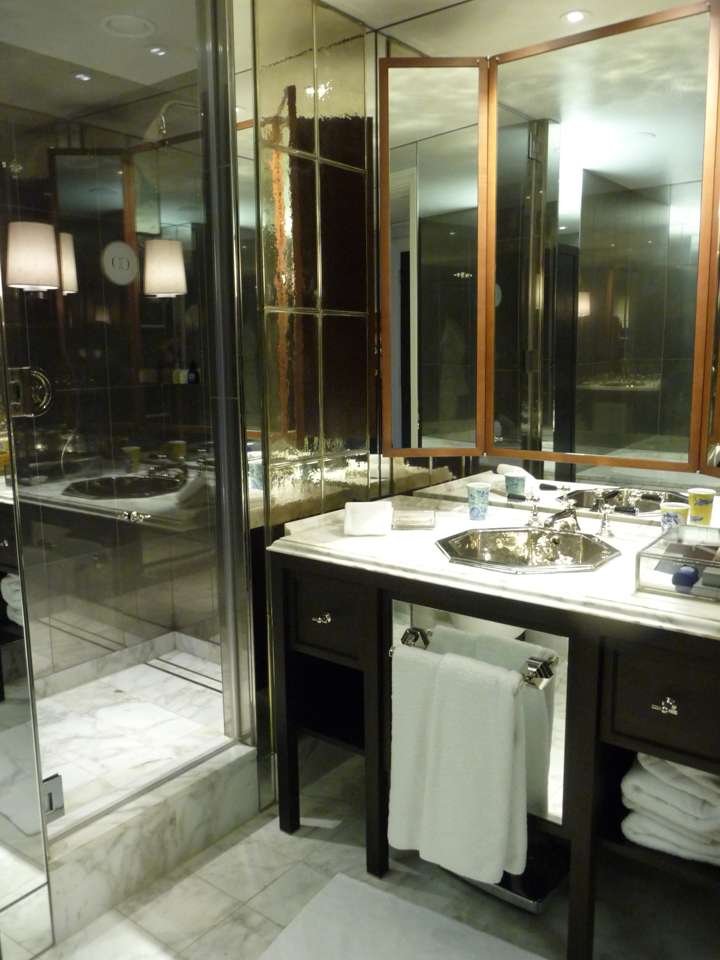 Beautiful bathroom - walk-in shower with mirrored walls and white marble floor