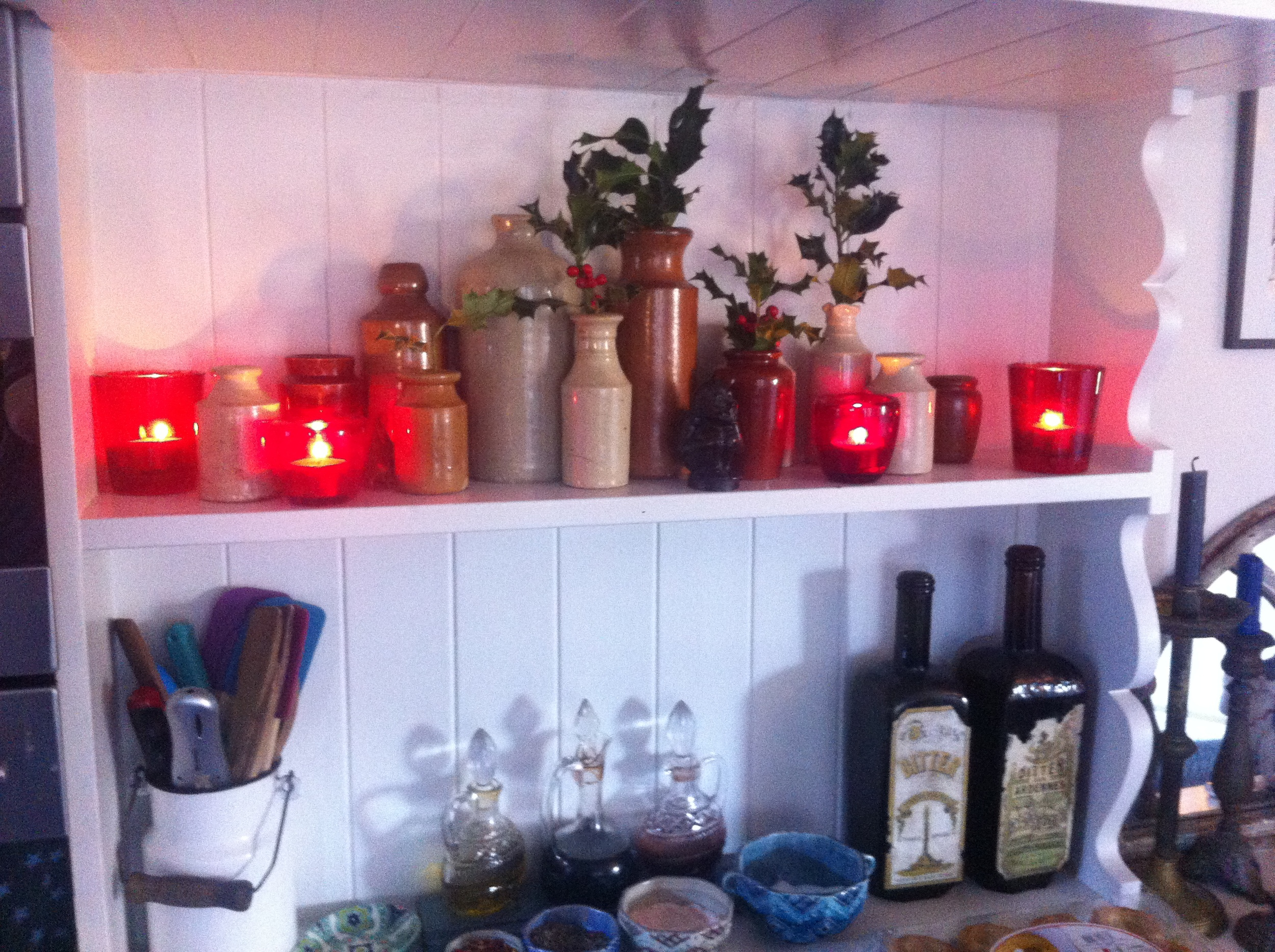 Tiny sprigs of holly in vintage bottles lit by a few candles