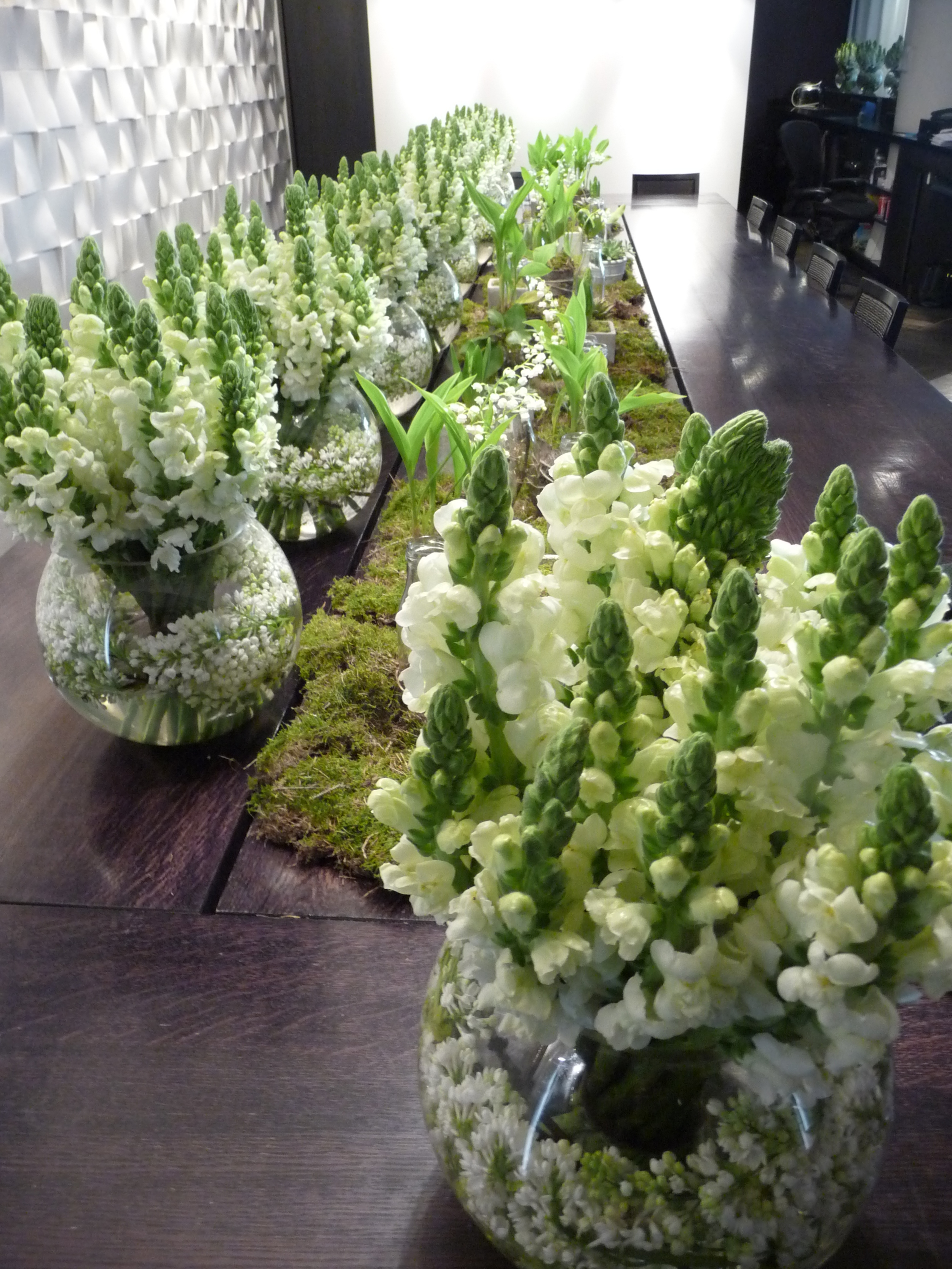 This long table display of flowers is absolutely amazing. White lilac is wrapped around the inside of each vase. There were small jars with succulent plants in them. One colour arrangements are always more impactful