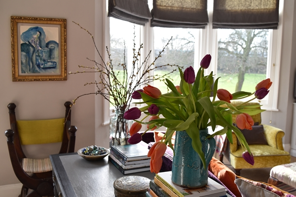 Here you can see vases of tulips and blossom in the sunlit sitting room. It's like bringing the outside in !