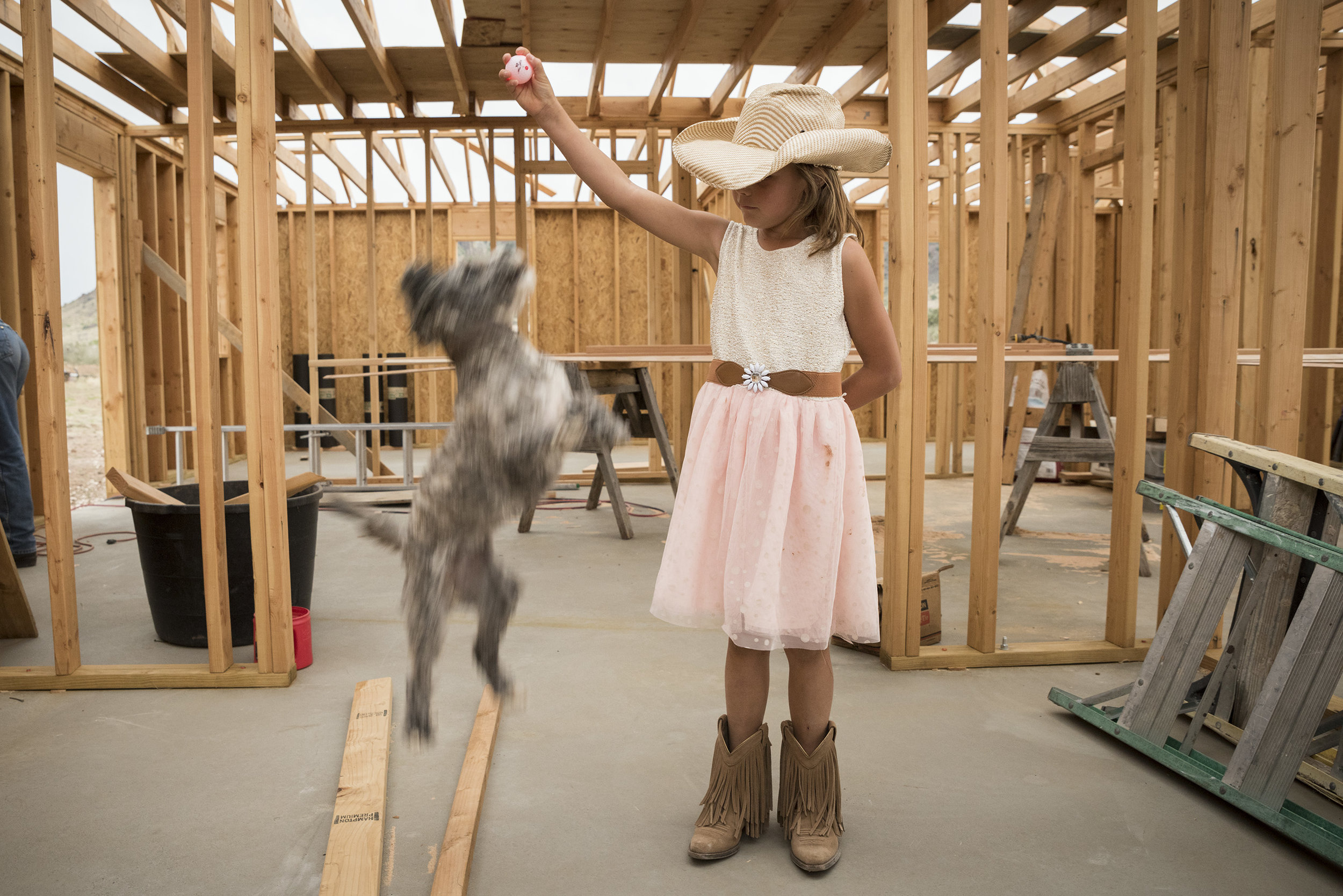 Young Girl Plays with Dog in House Under Construction