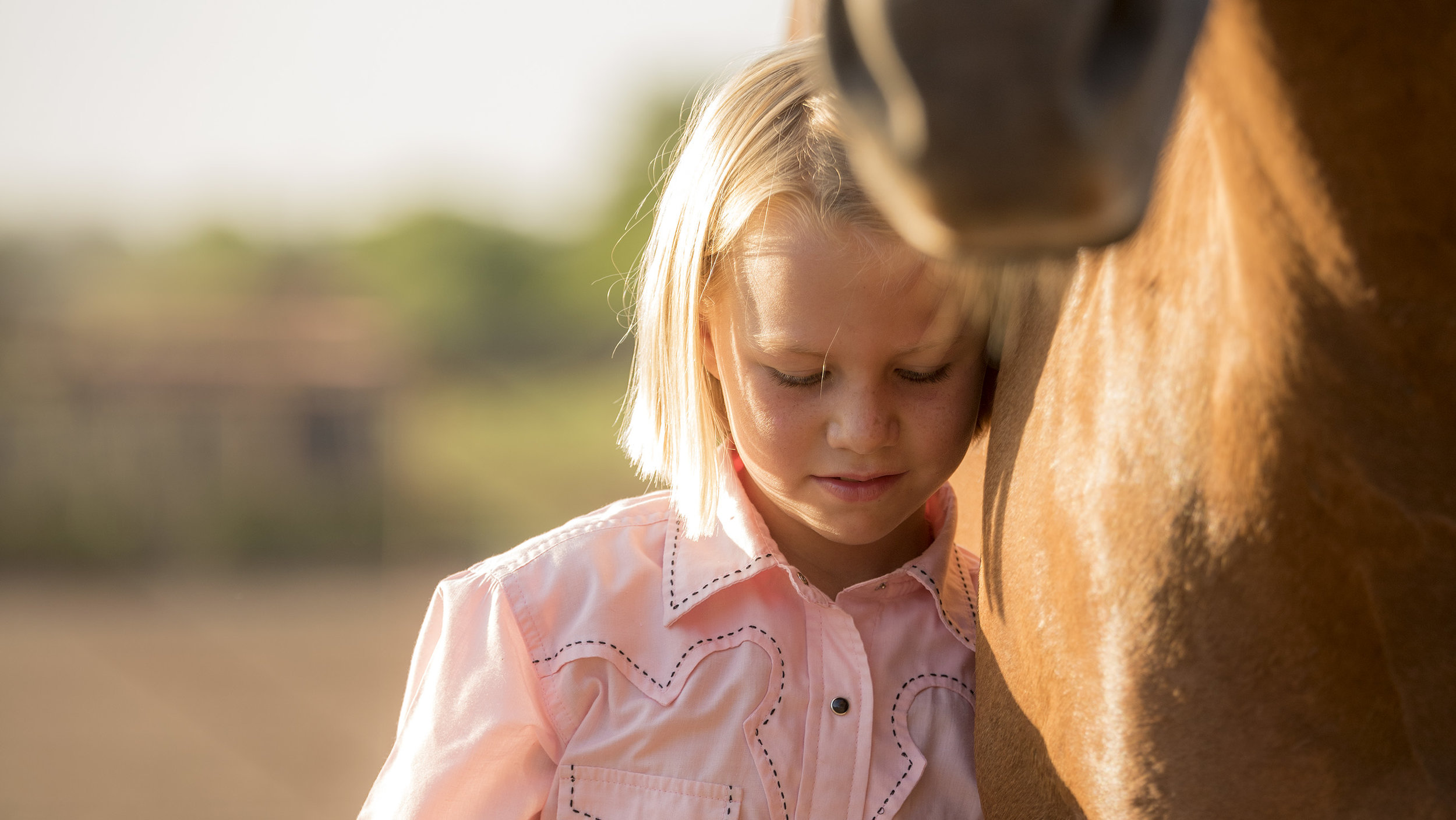 Ranching family with two young girls on horses in morning light at Cathedral Mountain Ranch, Alpine, Texas