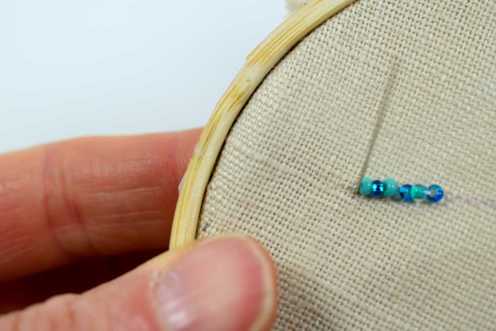 Bringing the needle back up at the beginning of  row of beads.