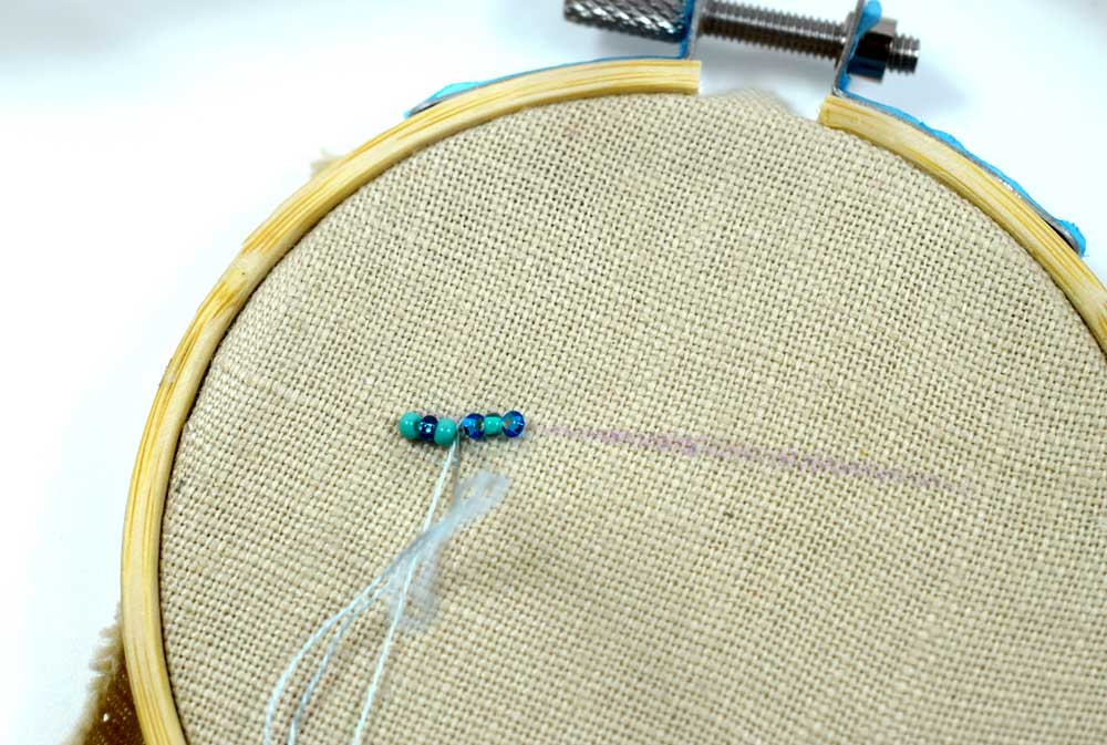 Bringing the needle back down into the fabric after running it through the first three beads.