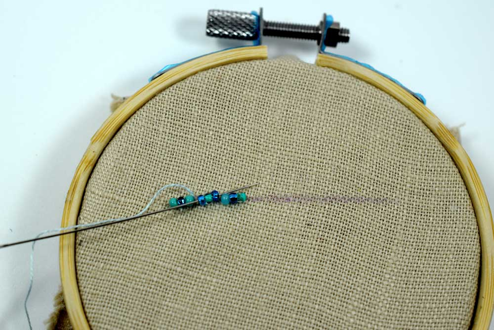Running the needle through the second set of three beads.