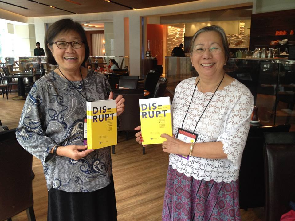 "Editors Maya Ong Escudero (left) and Maria Beebe showing off FWN's first Filipina leadership book, ""DISRUPT. Filipina Women. Loud. Proud. Leading Without A Doubt."" The book launch and press conference was held at A_Space Manila, Philippines, October 6, 2014, during the 11th Filipina Leadership Global Summit. (Photo courtesy of Maria Beebe)"