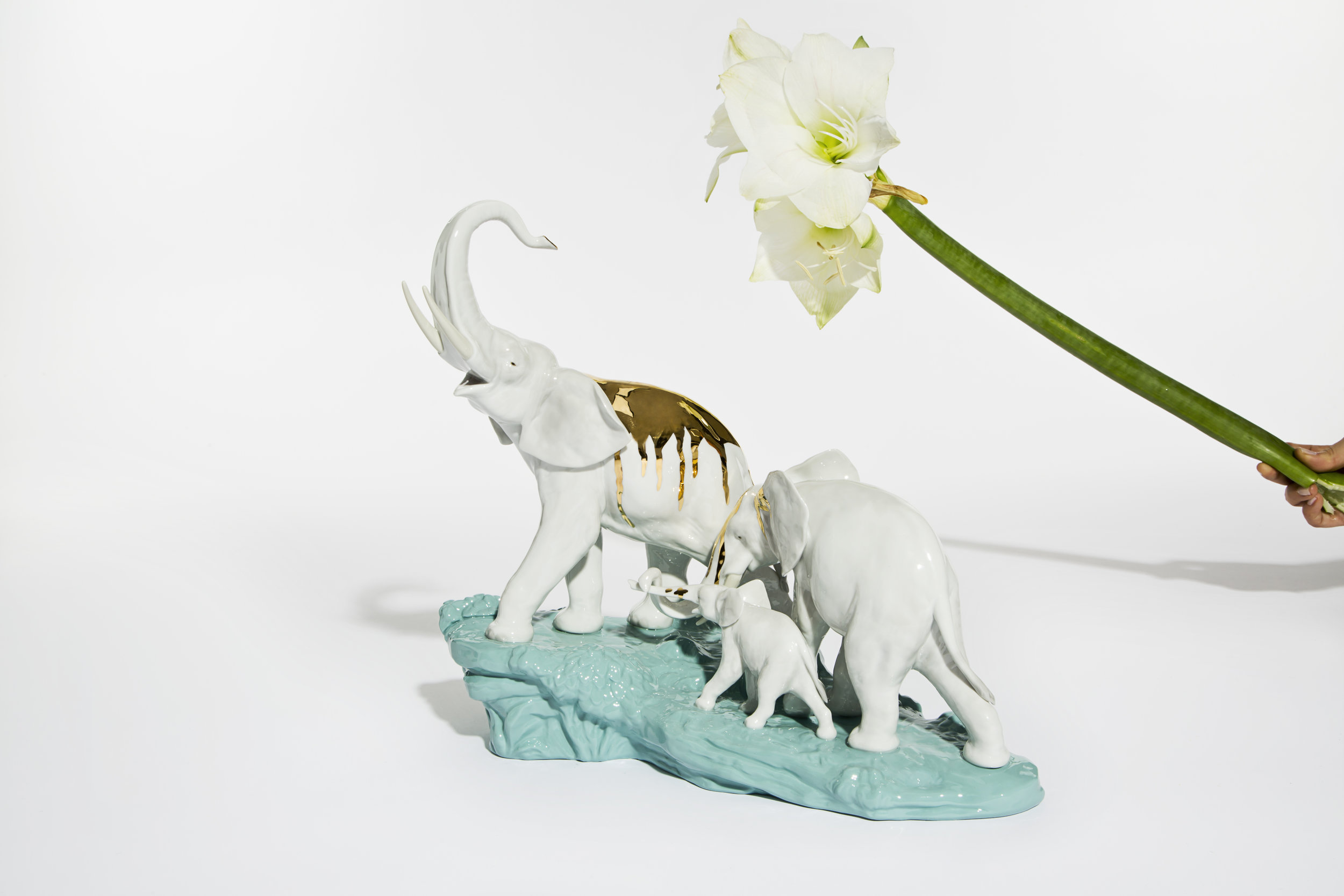 "ELEPHANTS WALKING  Clare Page & Harry Richardson for Lladrò    Dream and reality take form in a single suggestive scene Elephants Walking is part of the ""Animals in an Unreal World"" collection inspired by ""Animal Kingdom"", a film directed by David Michod. The gold accents simulate the flow of water, giving this statuette image an ethereal and joyful appeal. ""What we do for Lladrò, is what we loved to do most: take objects that have already fulfilled the function for which they were created and give them new life."" - Clare Page and Harry Richardson Clare Page and Harry Richardson graduated from the Liverpool School of arts and are serial collectors of figurines, cups, vases and different decorative objects. For the designers, each piece tells its own story, that is both magical and surreal. 'Pragmatism and imagination,' is the pairs motto and at the heat of each of their creations. Lladrò was founded in 1953 by Juan, José and Vicente Lladró. Every piece is the result of a laborious artistic process. To this day, the sculptors follow their own inspiration but also follow the leadership of the brand and if the work requires it, a meticulous process of research and documentation."