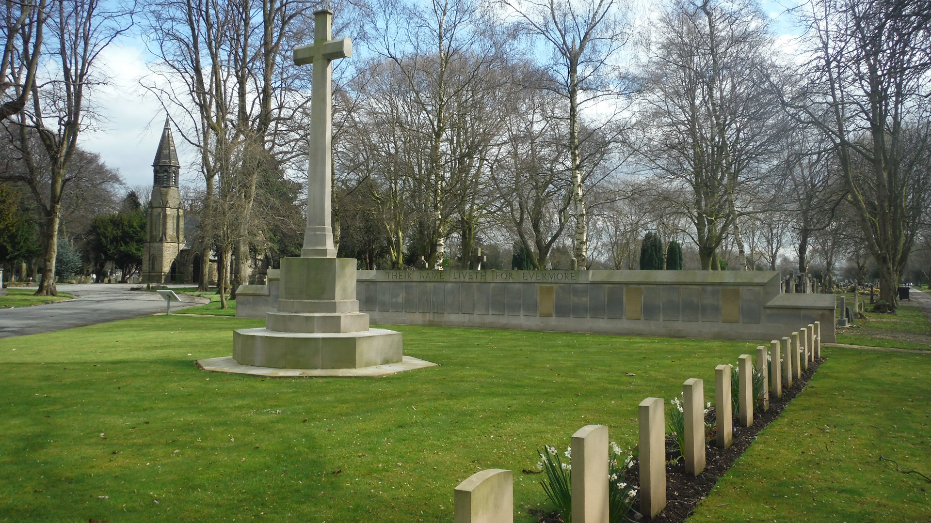 The memorial Screen wall behind the Cross of Sacrifice in Manchester Southern Cemetery