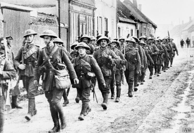 A platoon of 'D' Company of the 7th (Service) Battalion, Bedfordshire Regiment passing through a French village on its way to the line, shortly before the start of the offensive [Battle of the Somme 1916]. The officer at the head of his platoon is Lieutenant Douglas Keep, who was killed in 1917. Imperial War Museum image Q79478