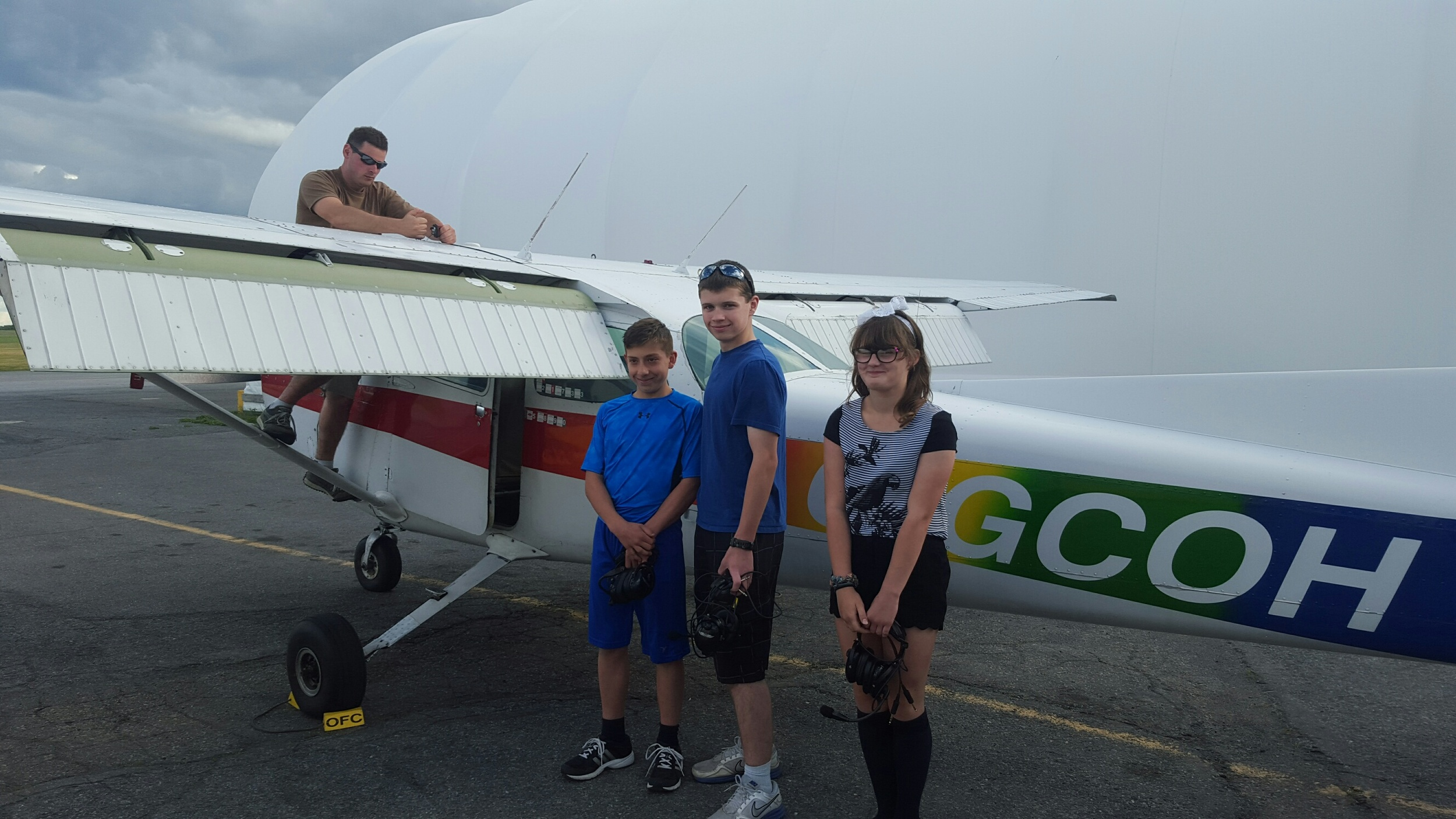 Lt (or Captain for these purposes) Keller completing the pre-flight inspection on Cessna C172N C-GCOH at the Ottawa Flying Club, at the Ottawa International Airport. / Cdt's Mercier, Briere, and Rhyne pose for a picture before departure.