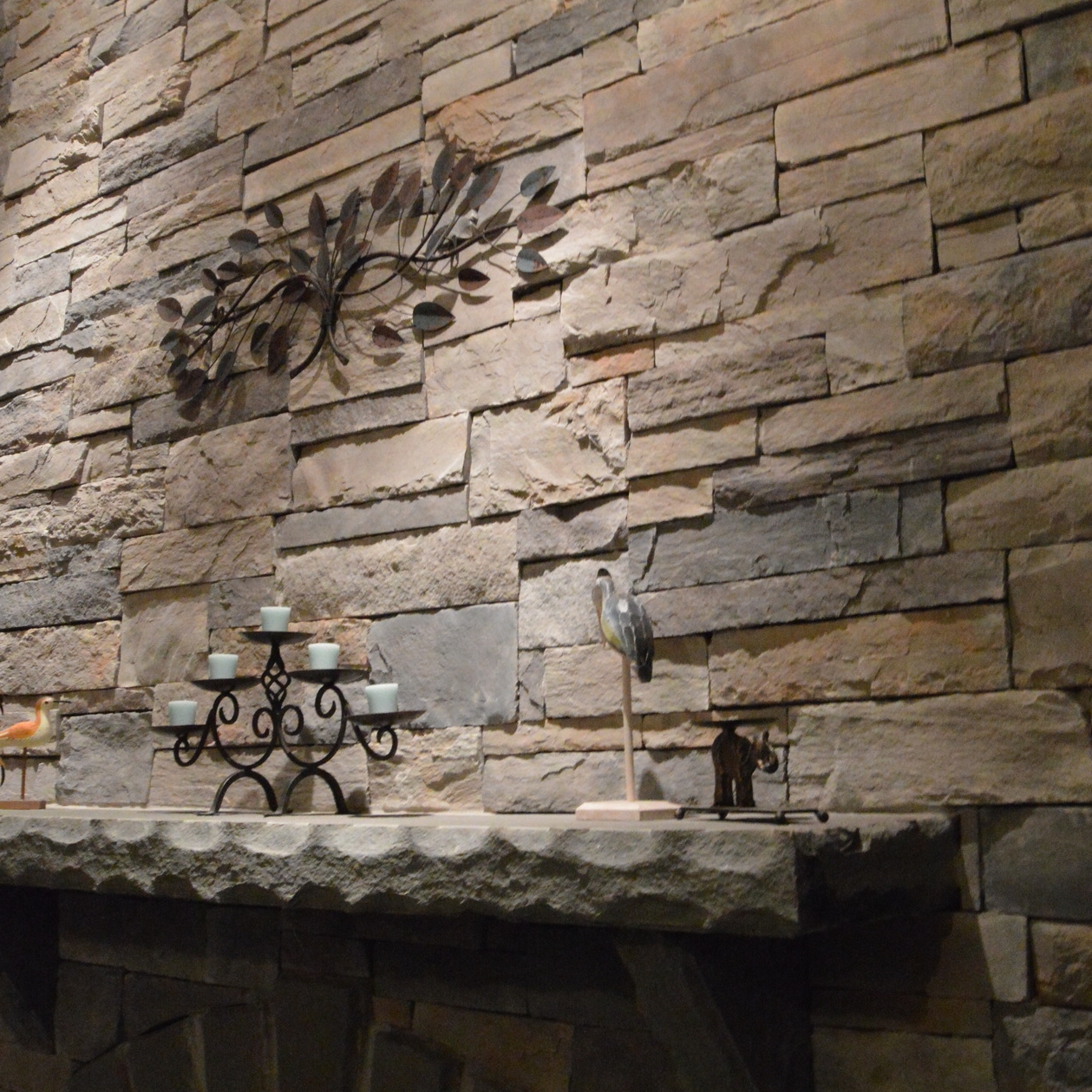 Fireplace finished with manufactured veneer stone and a custom cut and finished bluestone mantel and hearth. The Landworx team began with an unfinished bluestone slab that spanned over 7' in length.