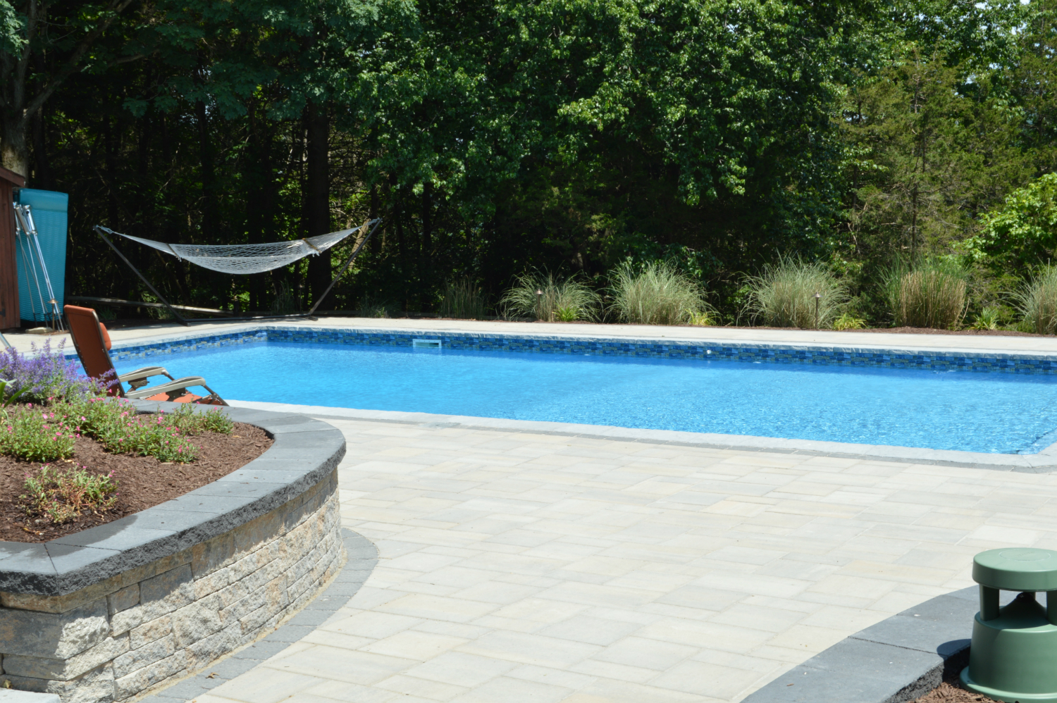Natural Stone and Greenery for a Welcoming Poolside Atmosphere in Florida, NY