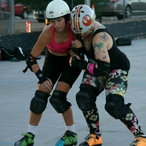 Ima Hazard practices with Madgina Dem Tatas in her hazard-cone-orange skates in 2015.