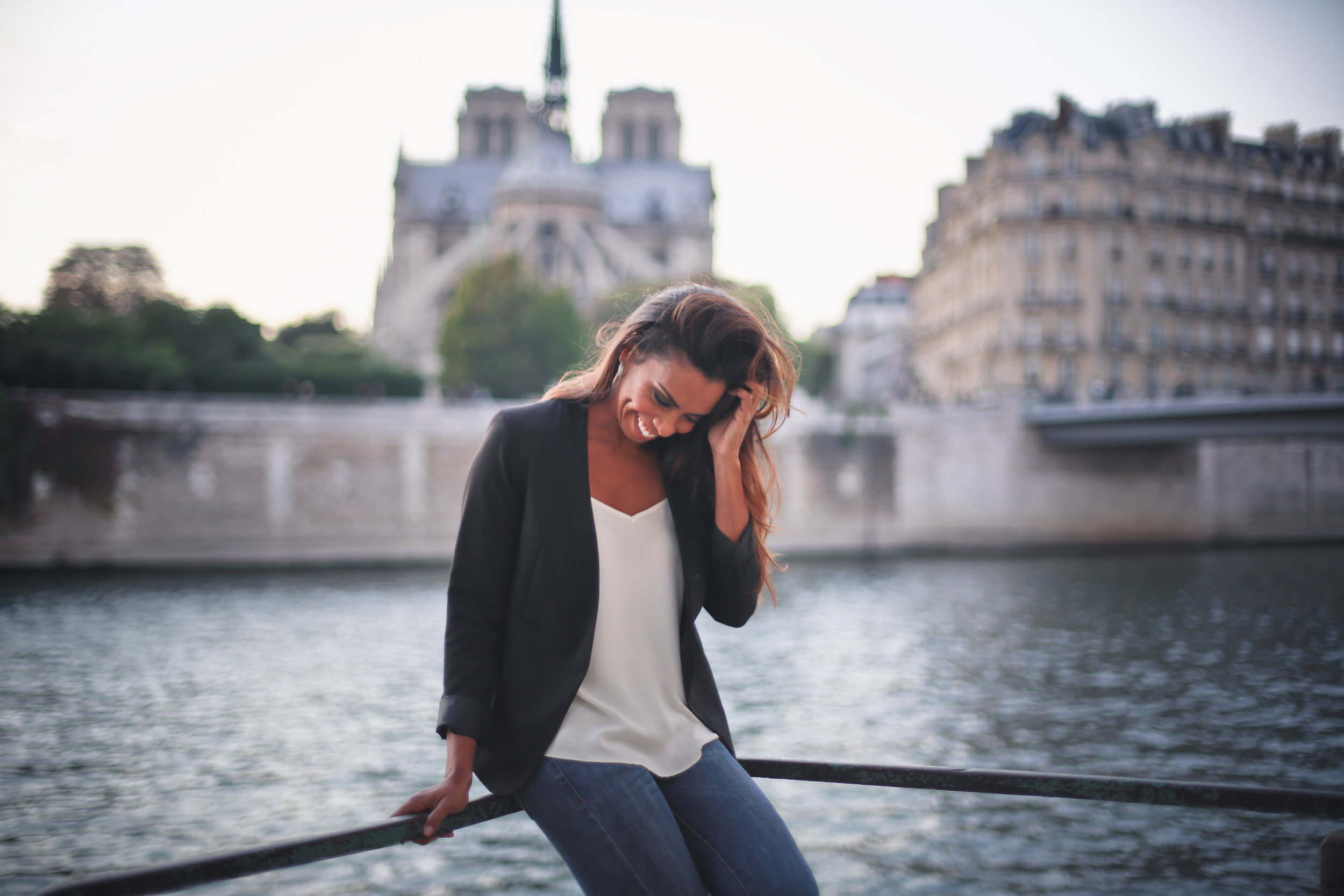 Paris vacation photo shoot with Flytographer. Woman sitting along the Seine river.