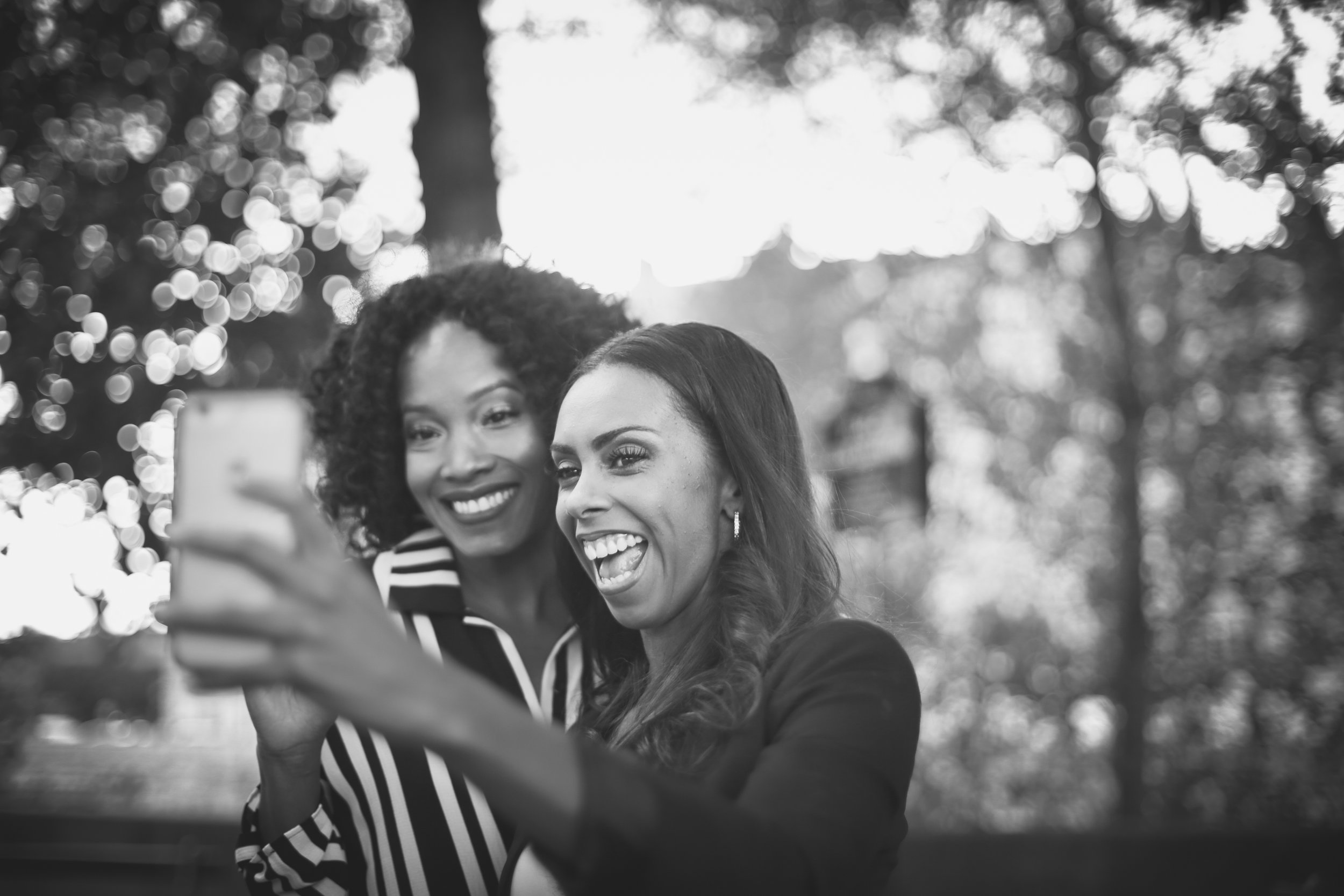 Flytographer. Paris vacation photo shoot. black and white photo. two friends taking a selfie.