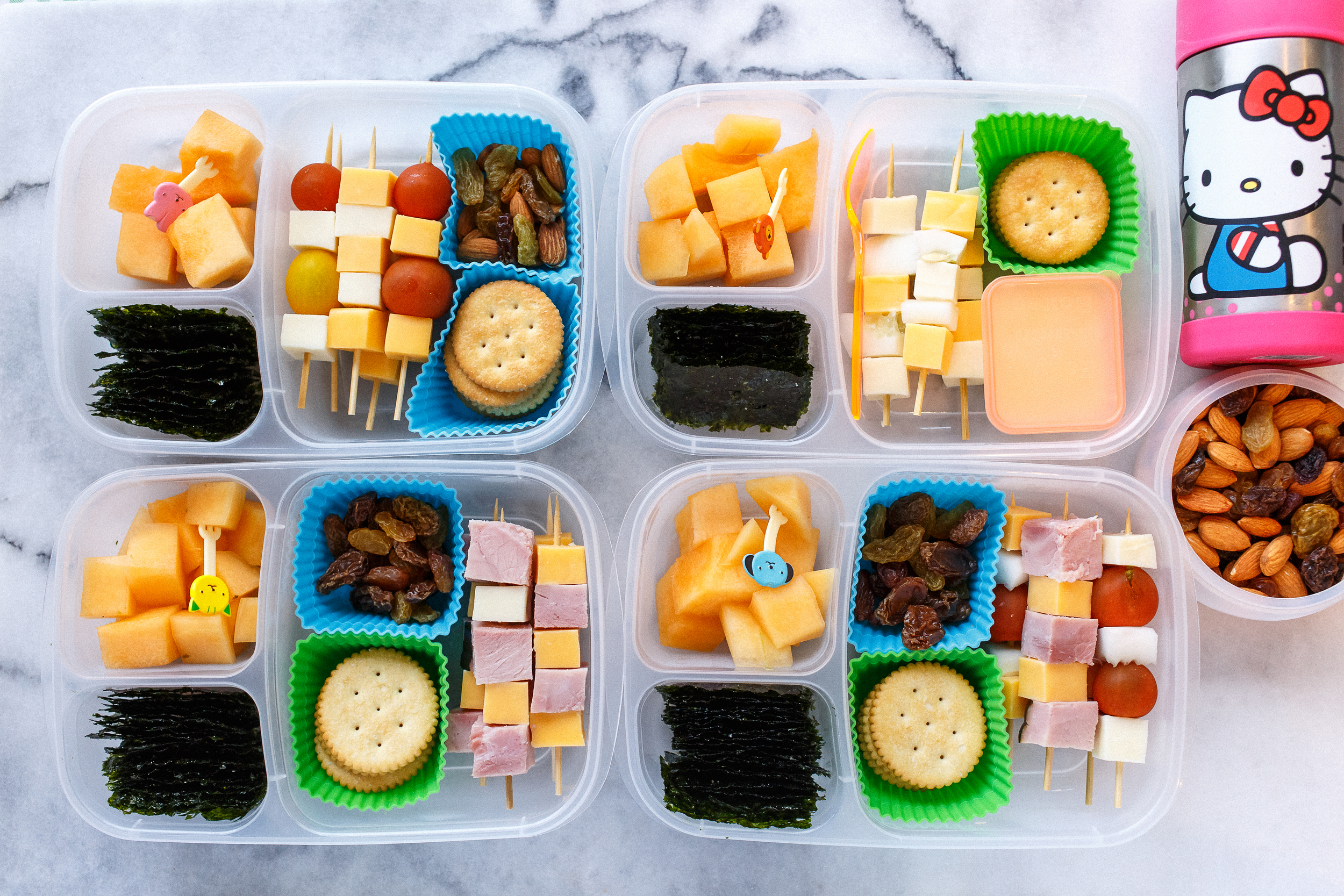 Little lunch skewers with a variety of ham, cheeses, tomatoes, and cucumbers, depending on who likes what. With raisins, seaweed snacks and melon. And the little one now has an extra side of nuts & raisins, and a thermos cup of milk.