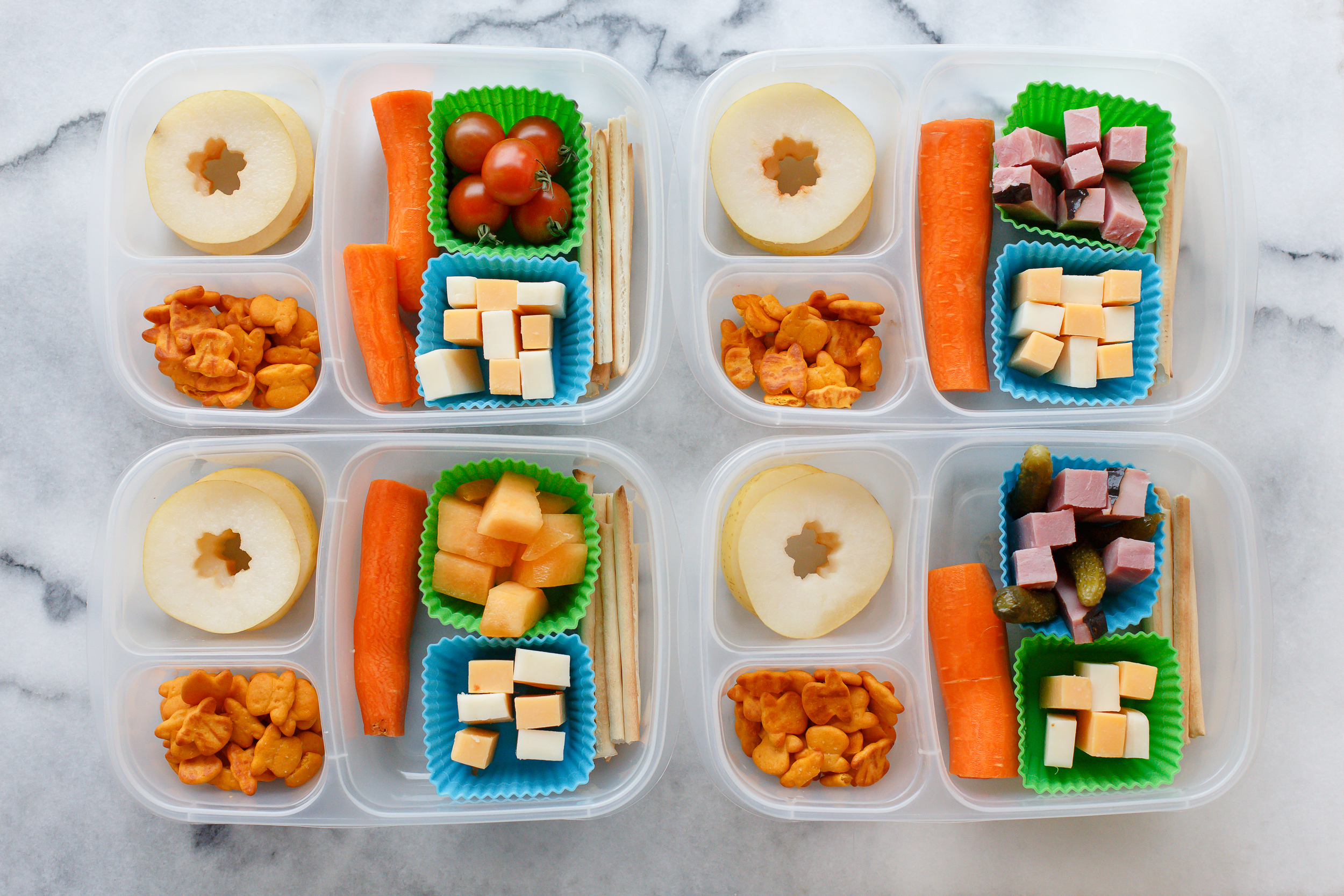 Tuesday lunch: sticks of cheese and ham. One has pickles, one has melon, one has tomatoes from the garden. With a big carrot, cheddar cows, and slices of pear.