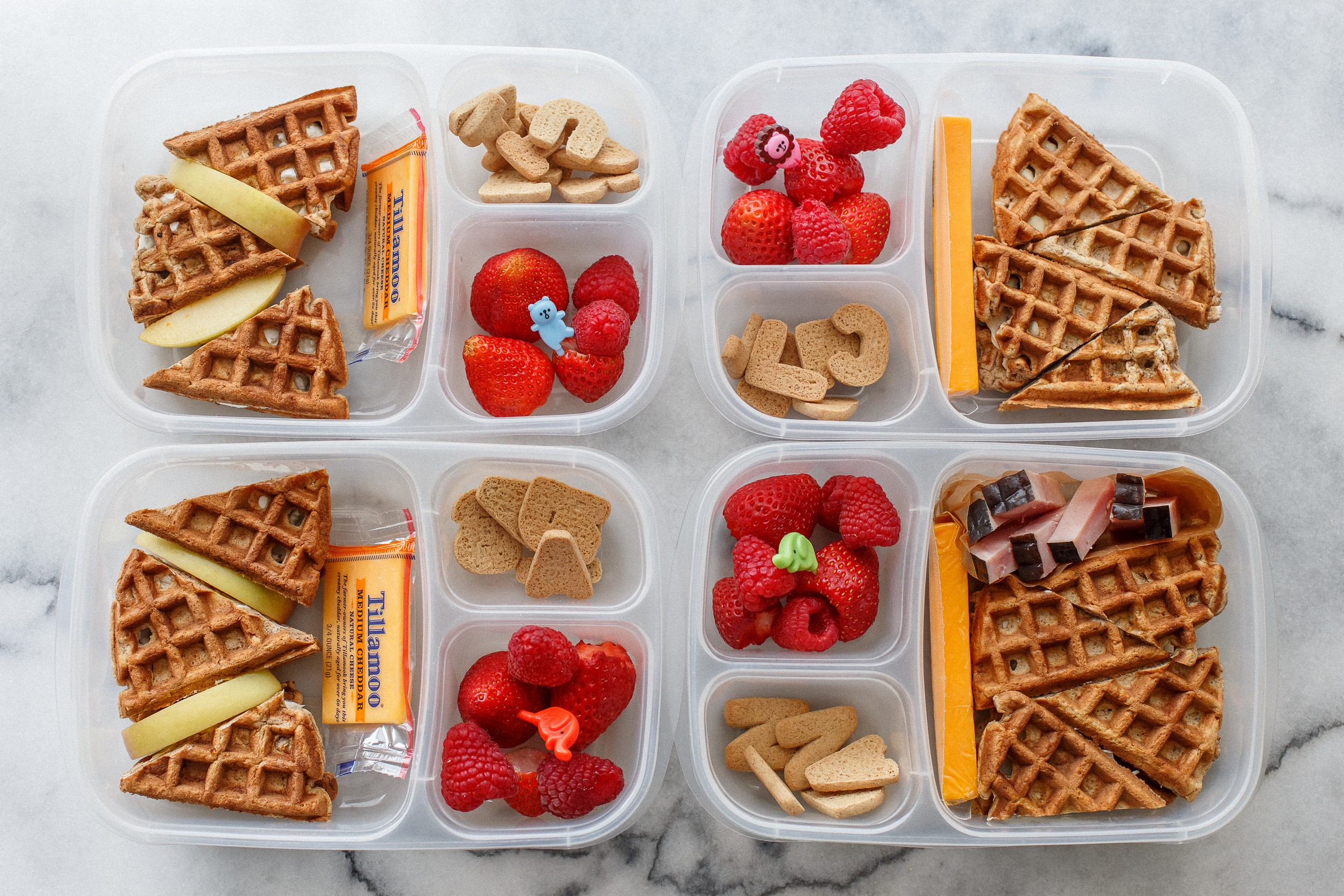 Wednesday is breakfast for lunch day at our house, and it's often the most popular lunch of the week. This one was no exception. Waffle sandwiches! Homemade waffles, I used whole wheat flour, oats, ground flax, extra egg, homemade almond milk, and just a little sugar - so they're pretty healthy. Three are spread with cream cheese, and one child has butter. They also have a cheddar cheese, berries, and some little cinnamon letter cookies to spell our their name. The boy has a little ham, and two of the girls have a couple slices of apple.