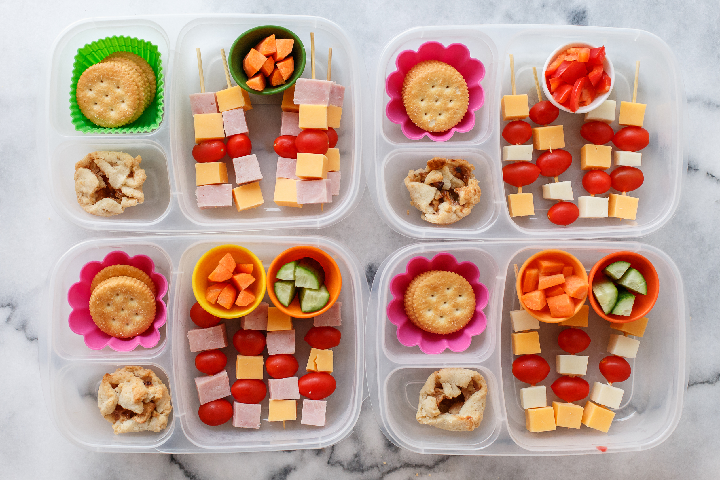 Little skewers of cheese and tomatoes, and ham for the meat eaters. Plus crackers and carrots, cucumbers for two, sweet peppers for one, and a mini apple pie for a special dessert treat!