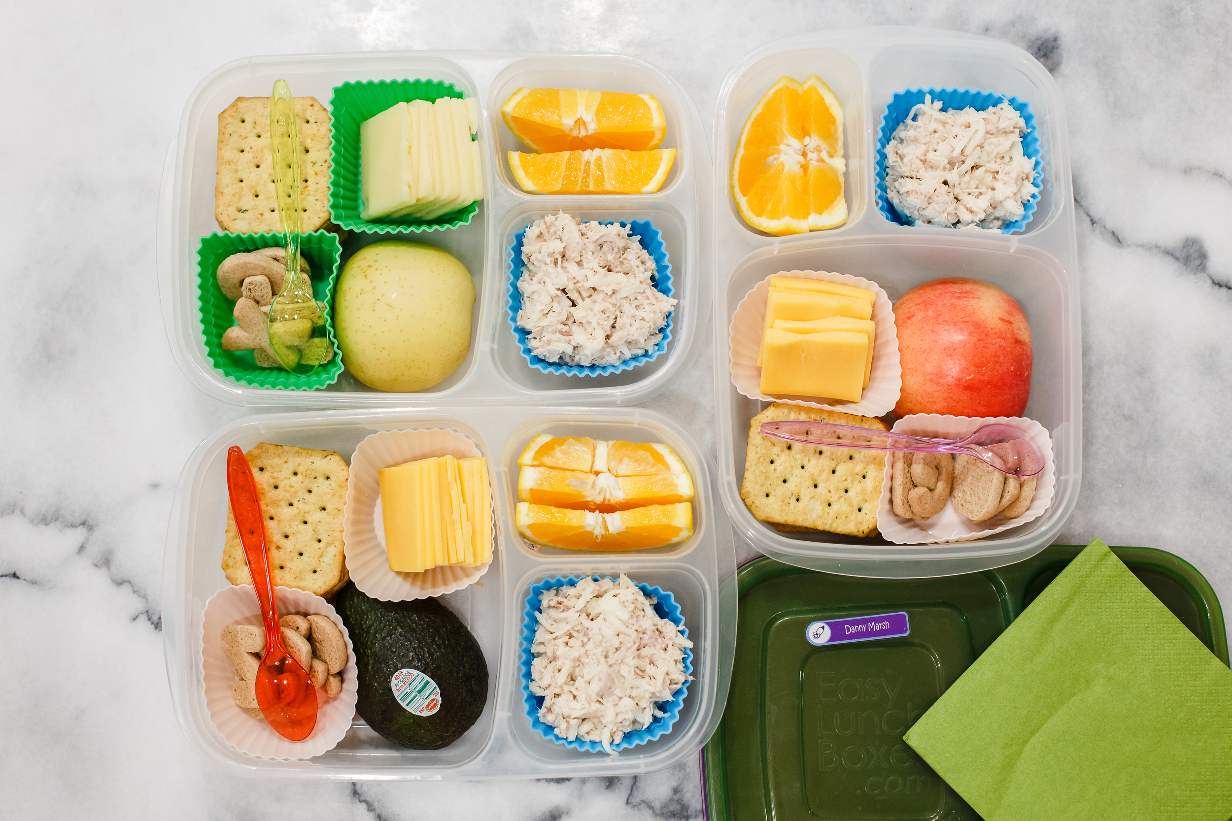 Thursday, lunches just for three: tuna salad, crackers, cheese, oranges and letter cookies. And one has half an apple, one has half an avocado, one has half a pear.