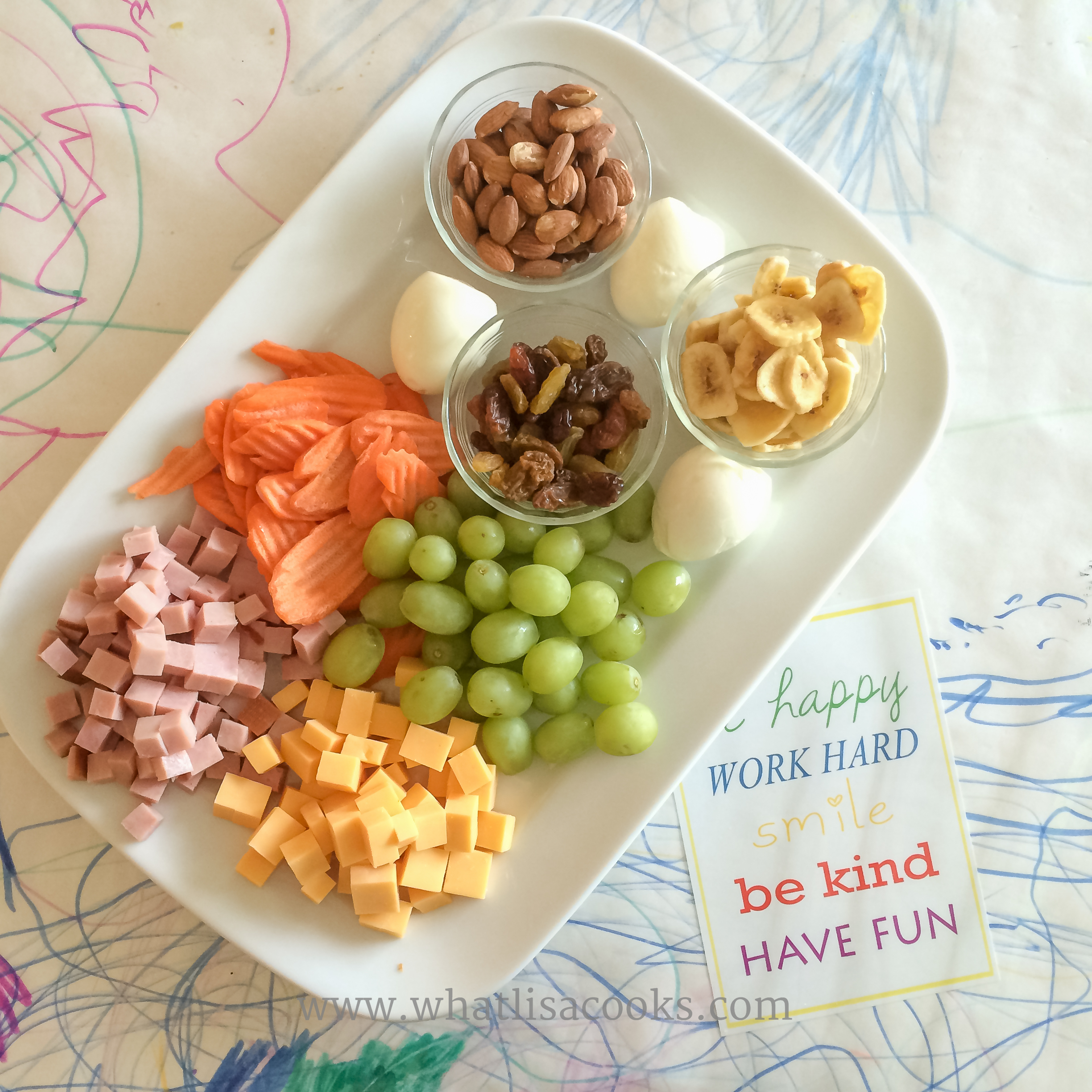 Cubes of ham and cheese, carrots, grapes, eggs, raisins, almonds, banana chips.