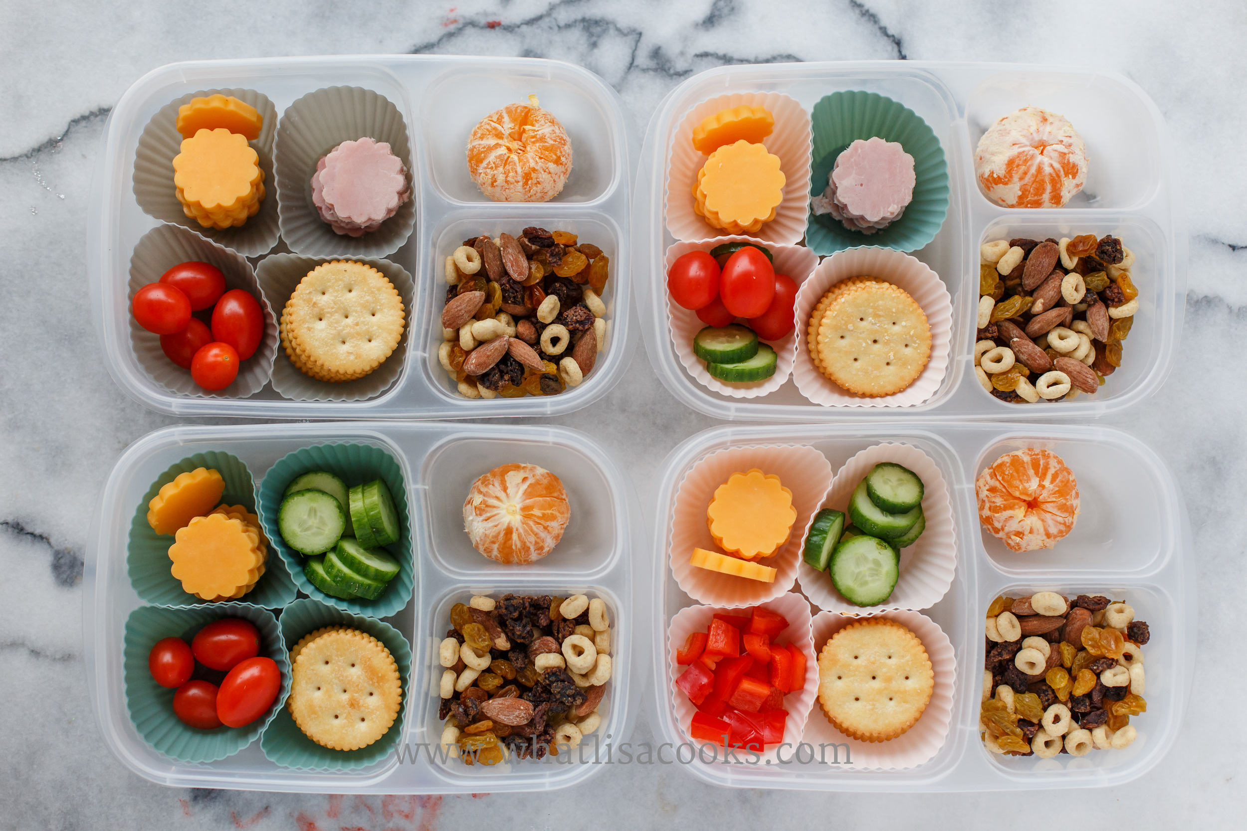 Lunchable: crackers, cheese, tomatoes, orange, two have ham, two have cucumbers, one has peppers, and they have a little trail mix on the side of almonds, raisins, and cheerios.