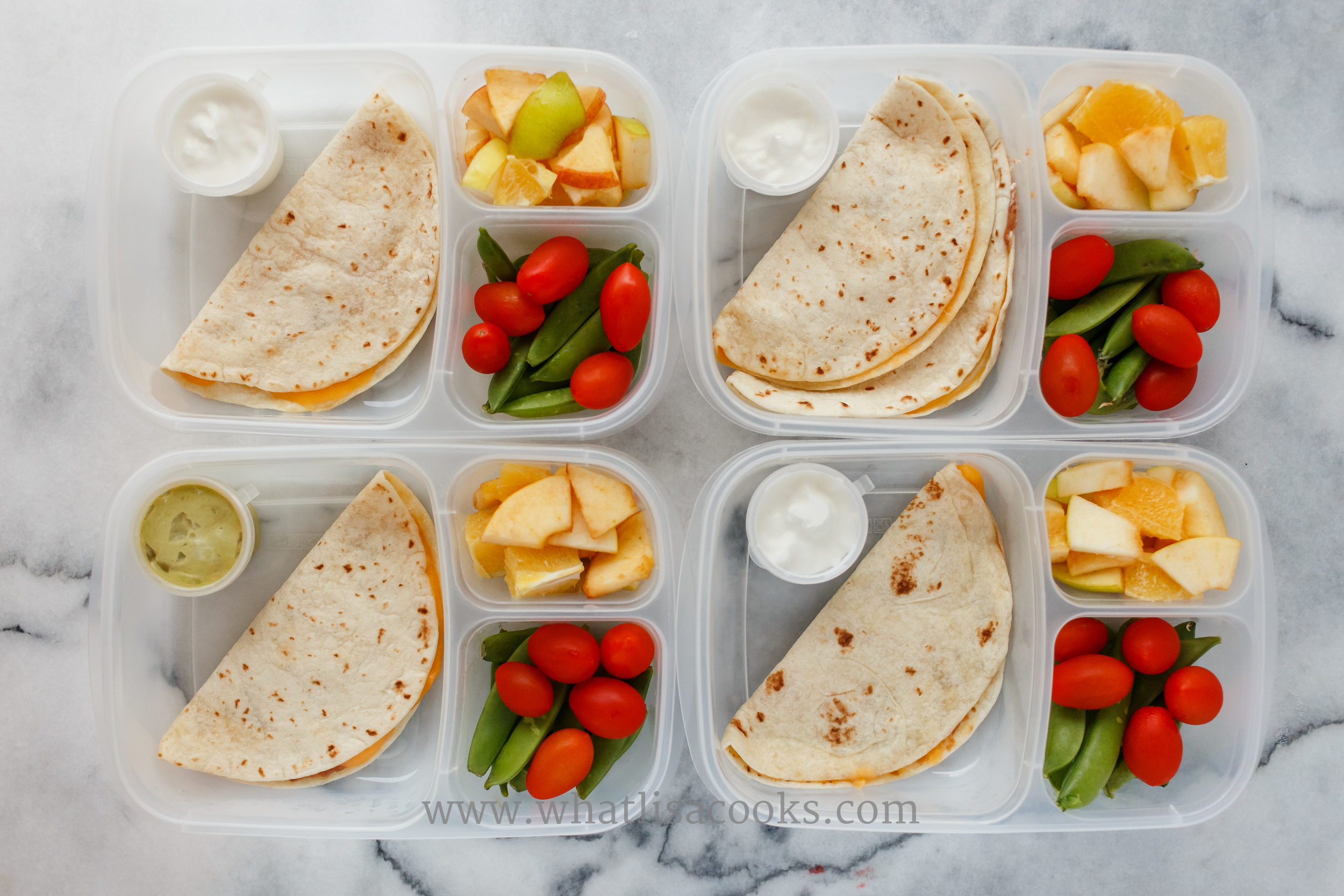 Quesadillas, two have beans and two have chicken.  Three have sour cream for dipping and one has guacamole.  Plus apple bites, sugar snap peas, and tomatoes.