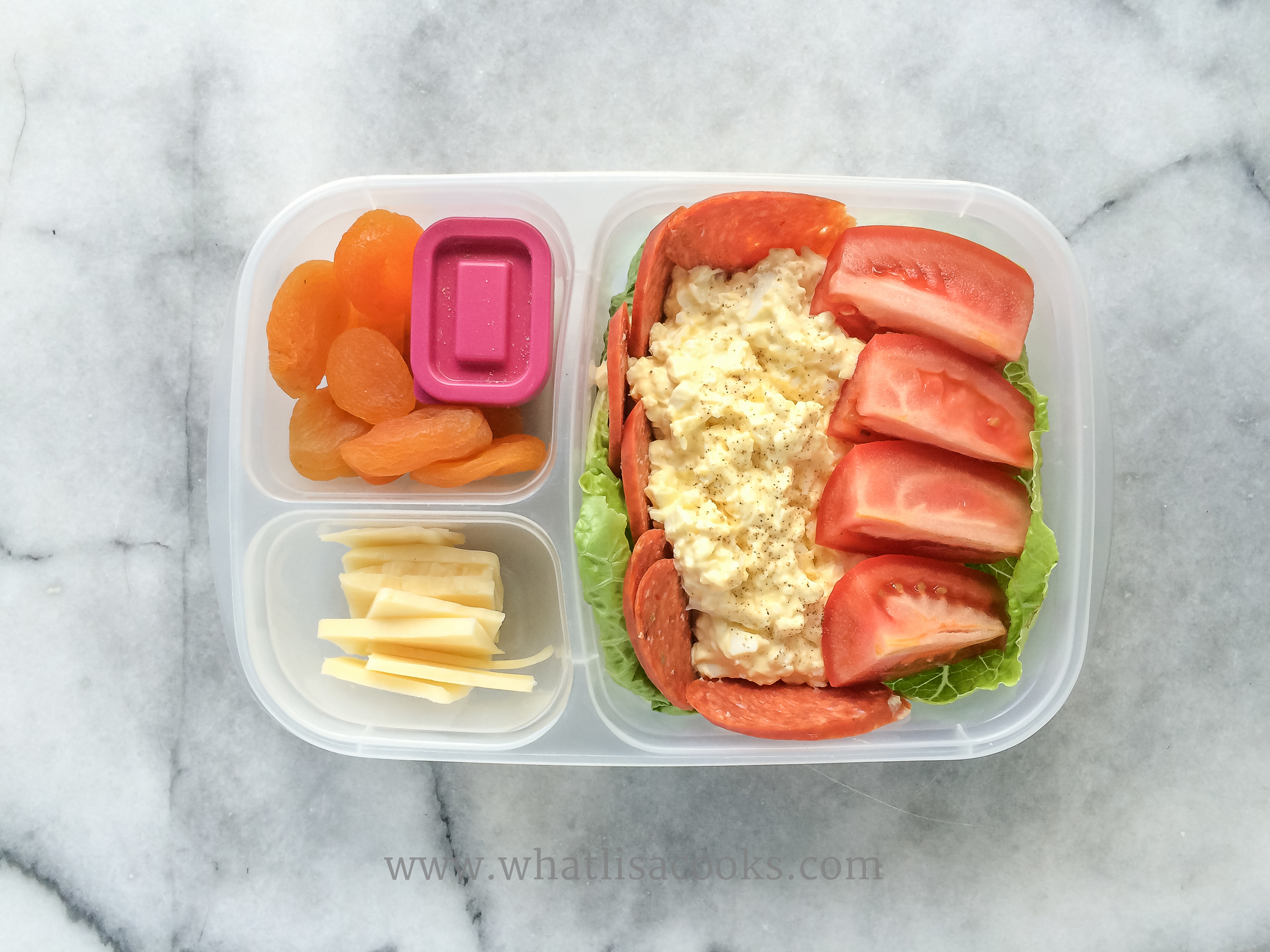 Egg salad - I like it simple, just mayo, salt, pepper.  On top of lettuce, with slices of pepperoni, a roma tomato quartered, slices of jack cheese, apricots.  The pink container has some extra salt for the tomatoes.
