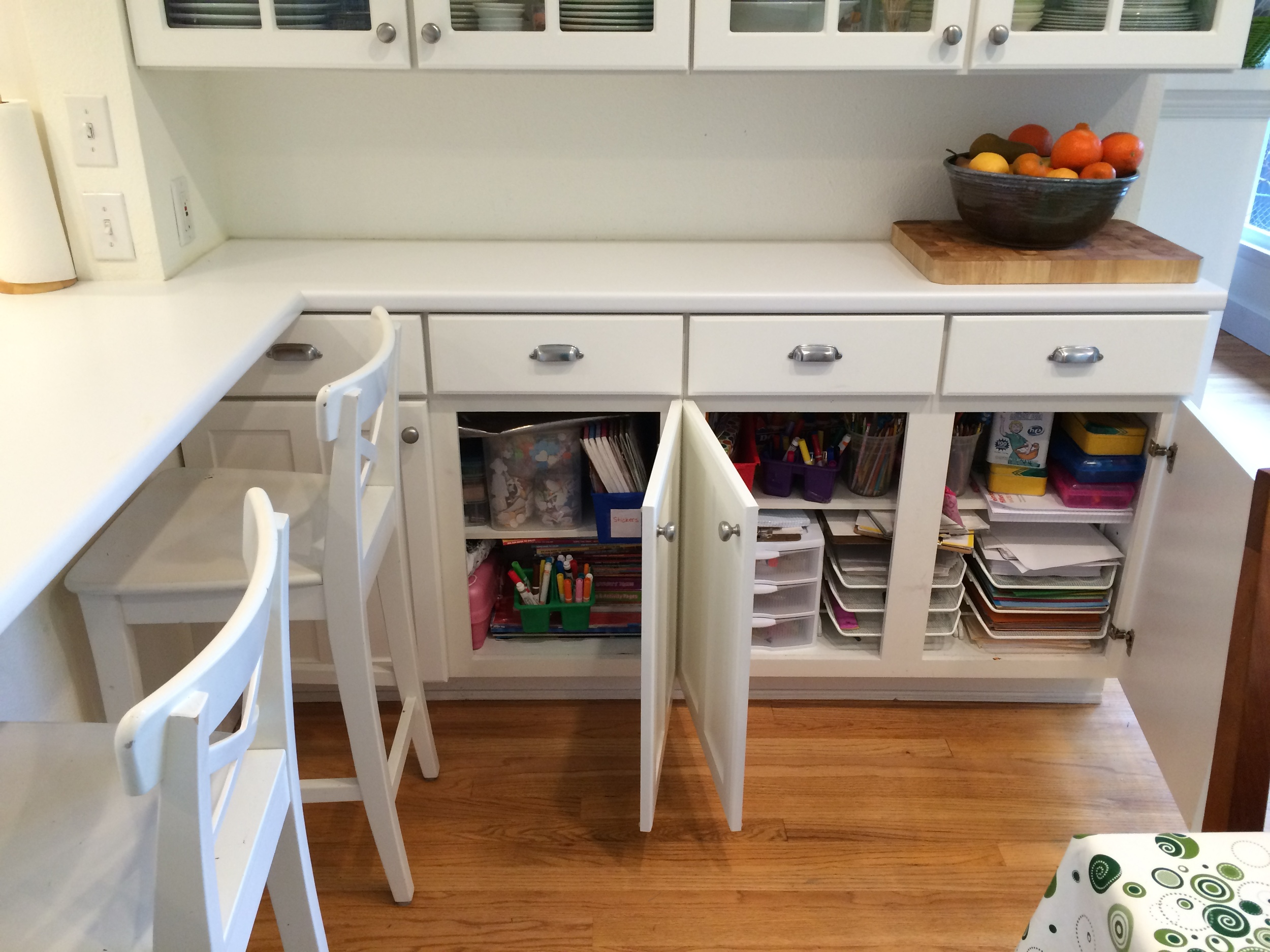 I decided to sacrifice some space recently and convert the lower cabinets to kids space.  This houses all our homework and craft supplies.  It was tricky to relocate some of the kitchen items I had here, but I'm glad I did because it gives my kids so much more opportunity to be creative when they have easy access to their supplies.  It also makes it easy for them to clean up when they are done.  My kids are old enough now that I feel comfortable with them having access to their art supplies for independent projects.  The only thing I don't keep down here is paint.