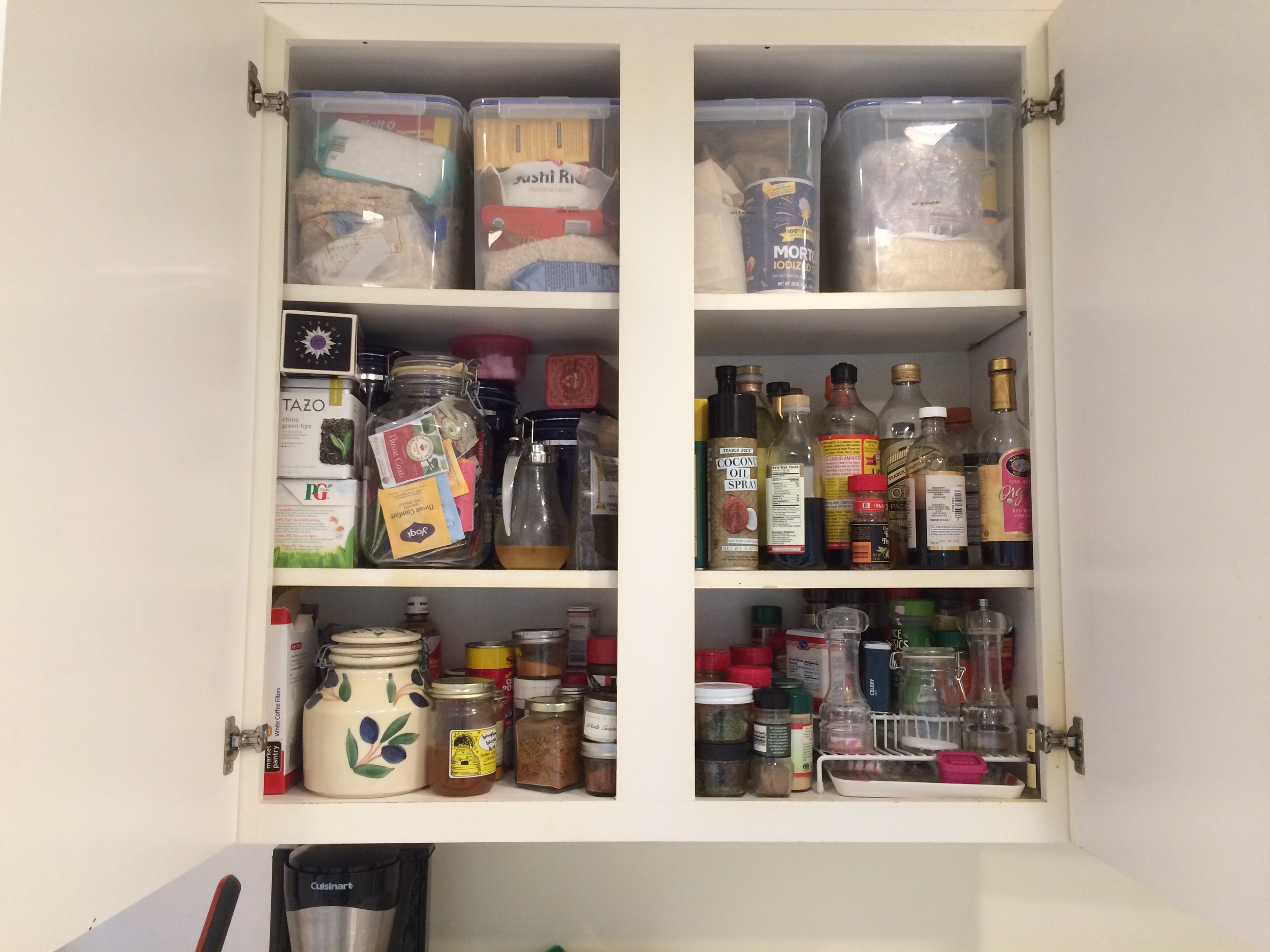 I have one upper cabinet to the left of the stove that has some cooking supplies - seasonings, oils, vinegars.  The containers at the top have baking supplies, rice, hot cereals.  And this is where we keep the coffee and tea.