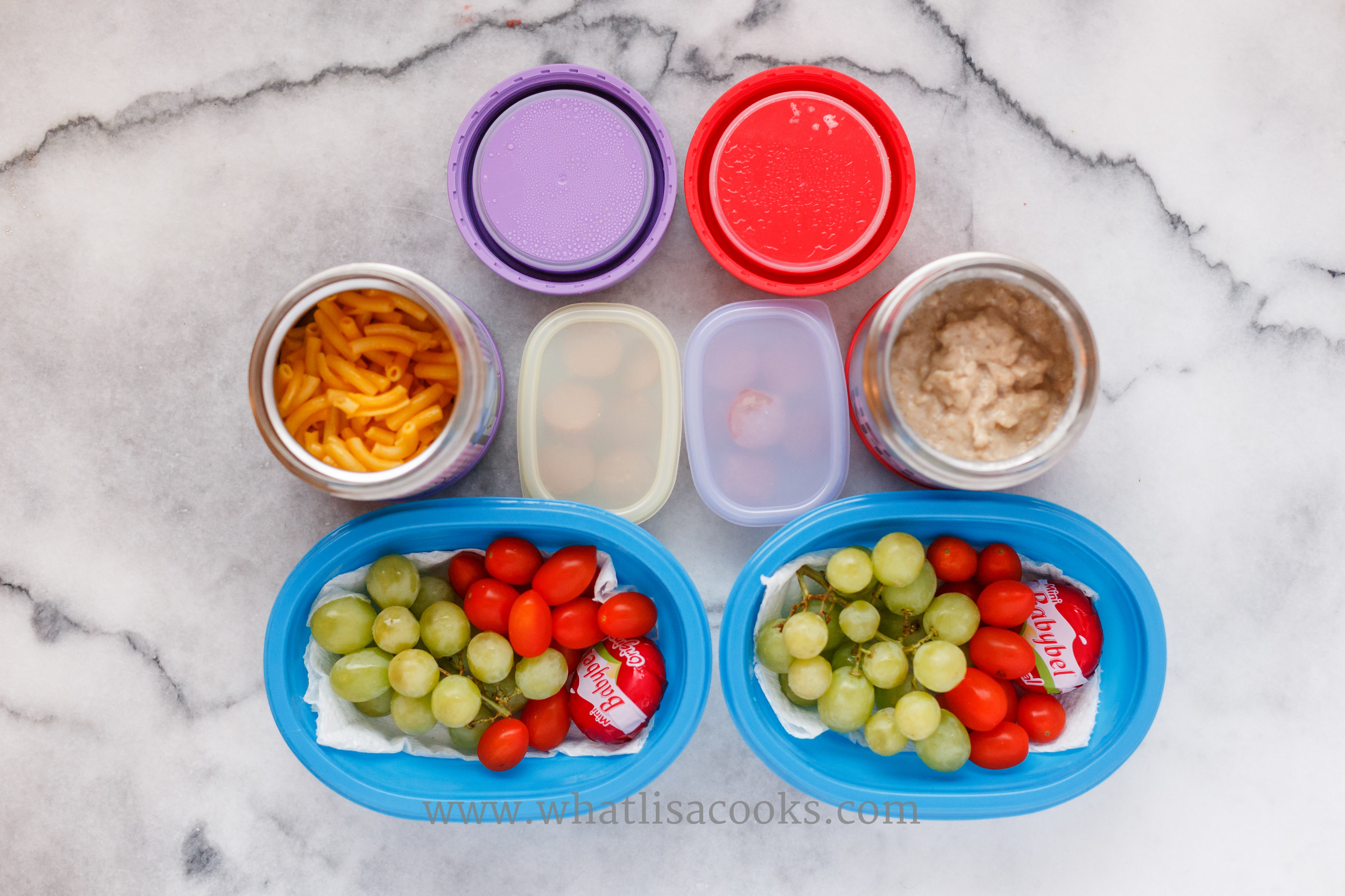 One has leftover macaroni and cheese, the other has my homemade instant oatmeal. On the side they have grapes, tomatoes, cheese, and a few bites of hot dog. They ate nearly every bite.