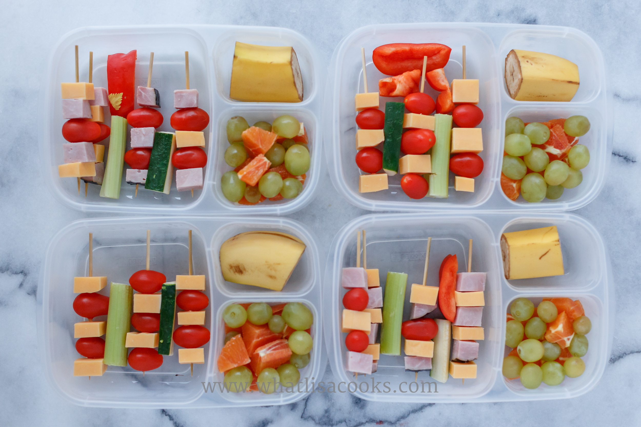 Skewers of ham, cheese, tomato, with carrot, celery and zucchini in between.  On the side there are grapes, orange bites, and banana.