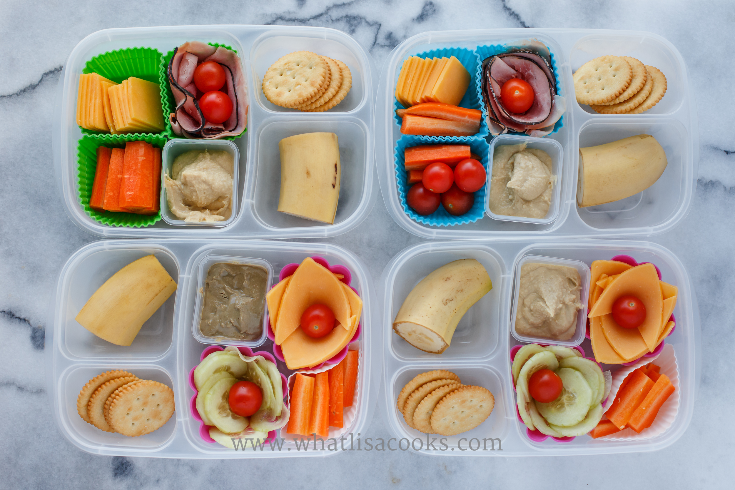 Two of these have cheese, ham, hummus, carrots, tomato and banana. One has the same but cucumbers instead of ham. The fourth has the same as that but swapped out sunbutter for the hummus. Serve with gluten free crackers.
