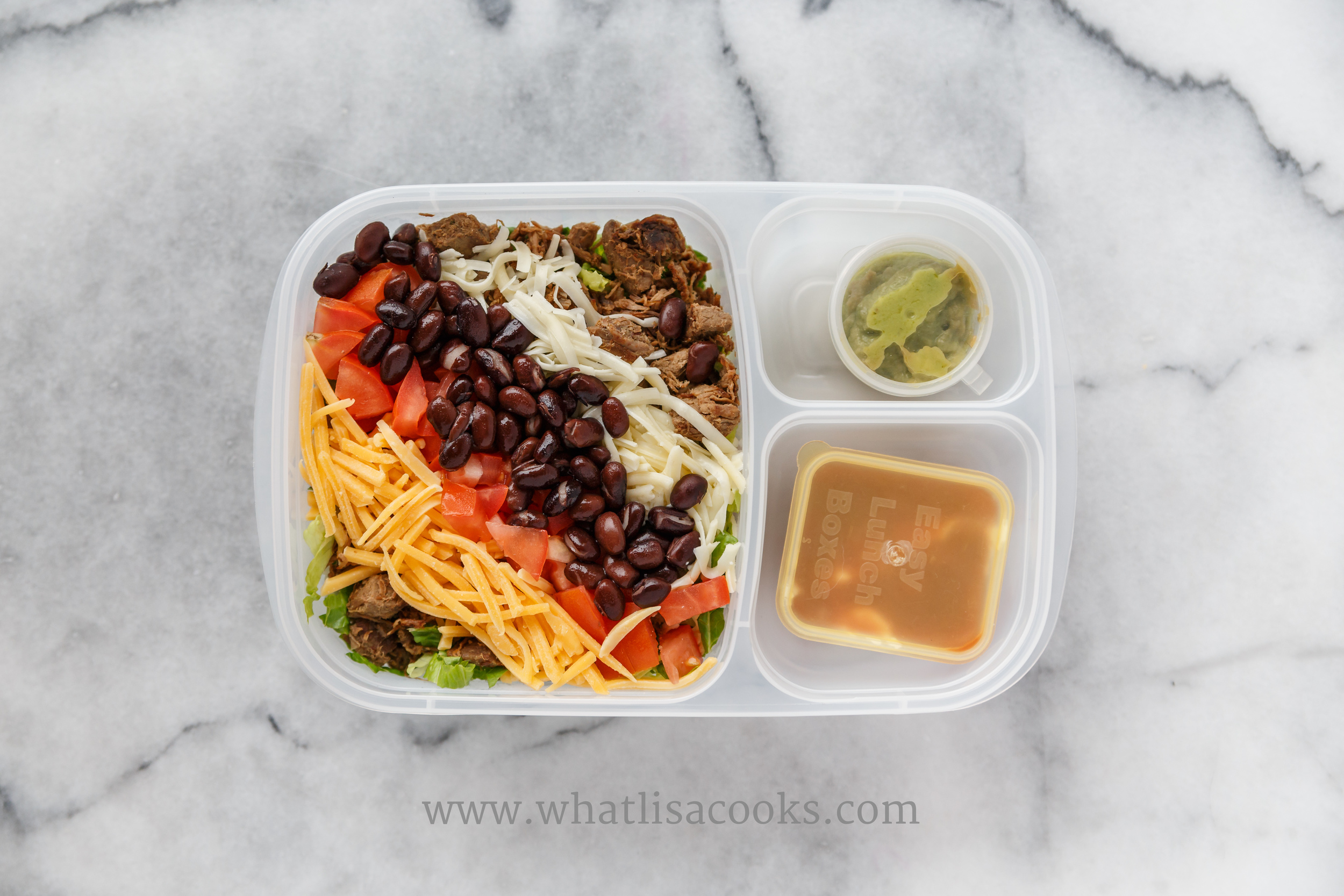 Taco salad made from dinner leftovers: lettuce, shredded beef, black beans, cheddar cheese, jack cheese, tomatoes. On the side there is one container of sour cream + salsa, and one of guacamole, to be mixed in to the salad for dressing.