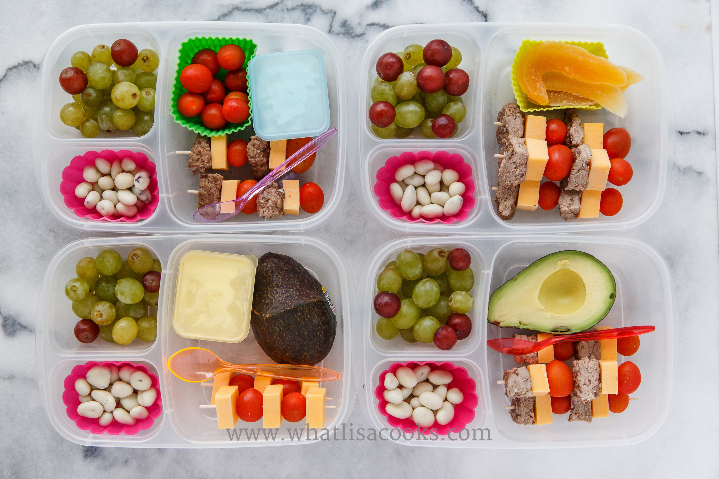 Bunless burger sticks: bites of homemade hamburger patty, cheese, tomatoes on skewers.  Grapes and yogurt covered raisins on the side.  Two have avocado, one has dried mango, one has yogurt, one has cottage cheese.